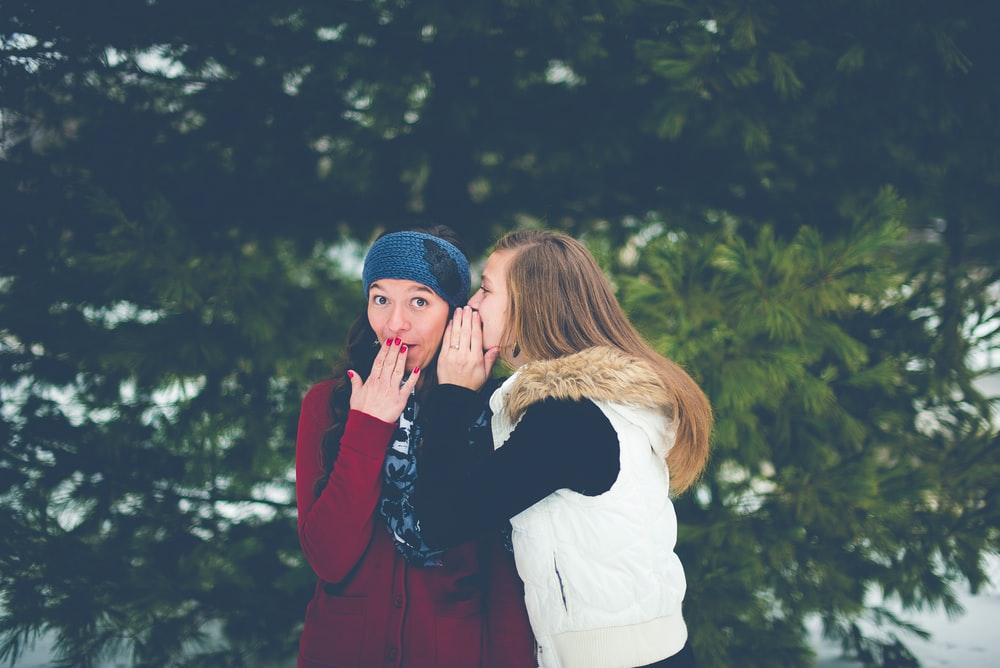 Two young friends whispering secrets to each other in winter
