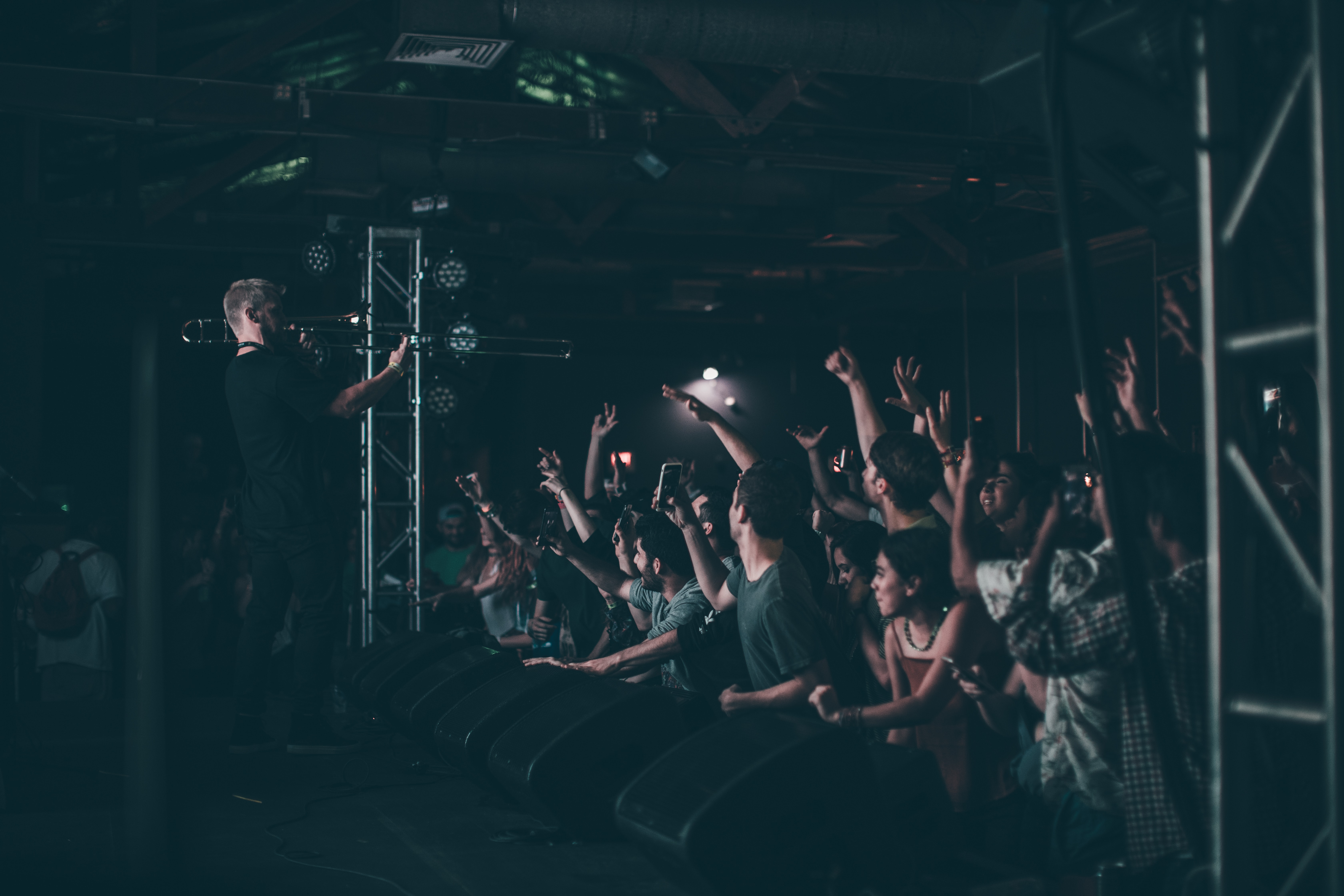 A man playing the trumpet in front of an enthusiastic young audience in Austin