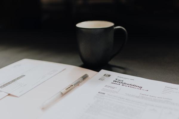 咖啡杯旁边打开的文件夹与扣税纸