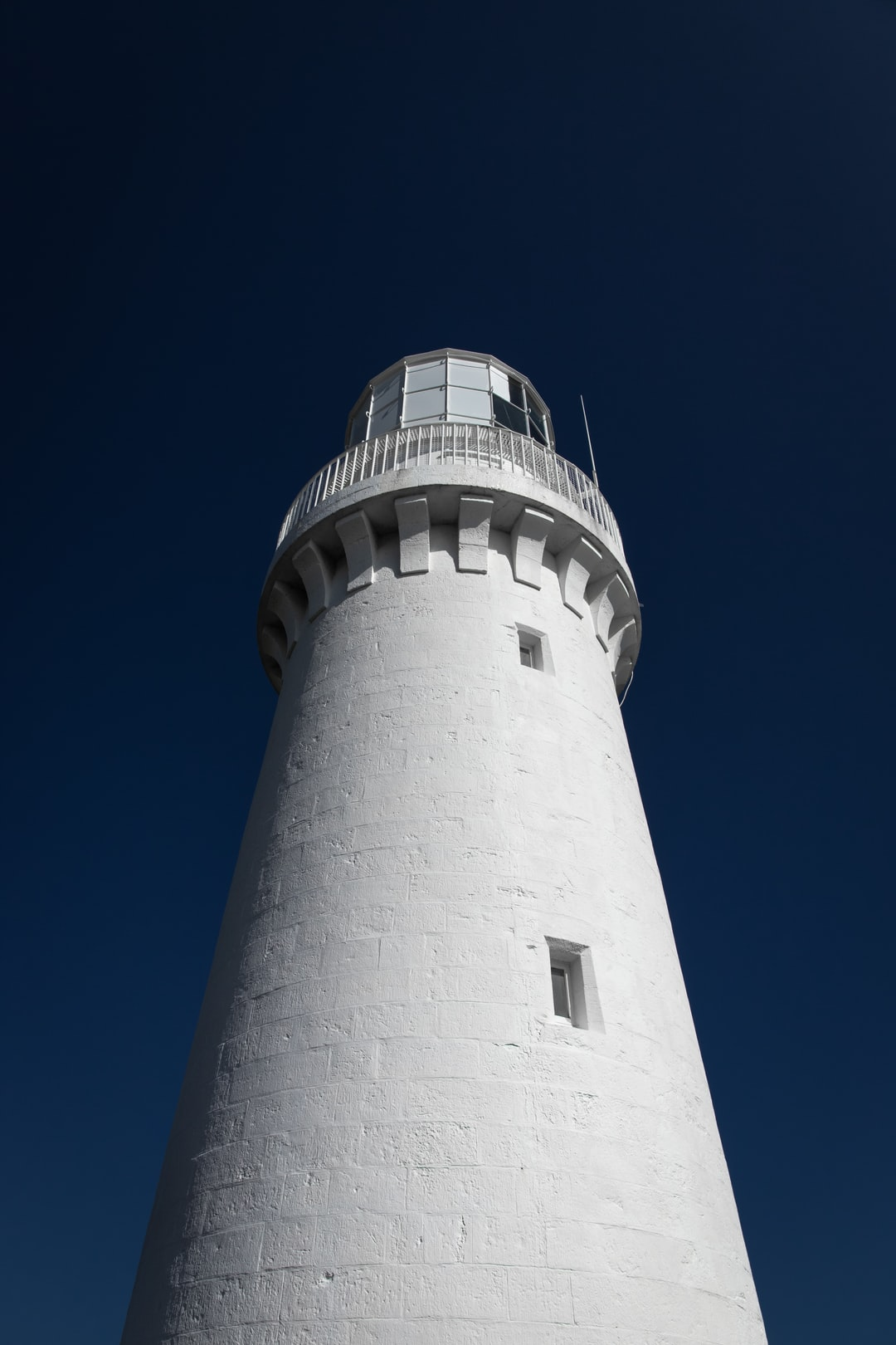 White and black concrete lighthouse under blue sky...