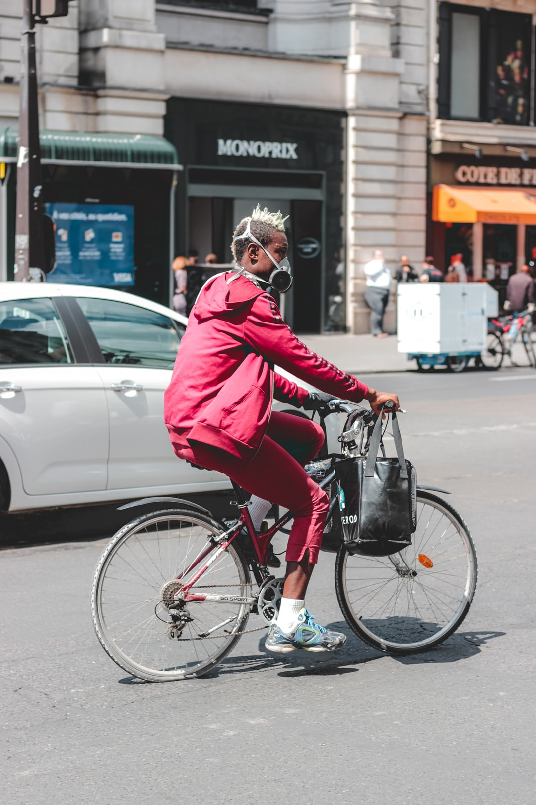 Man in red jacket riding on bicycle during...