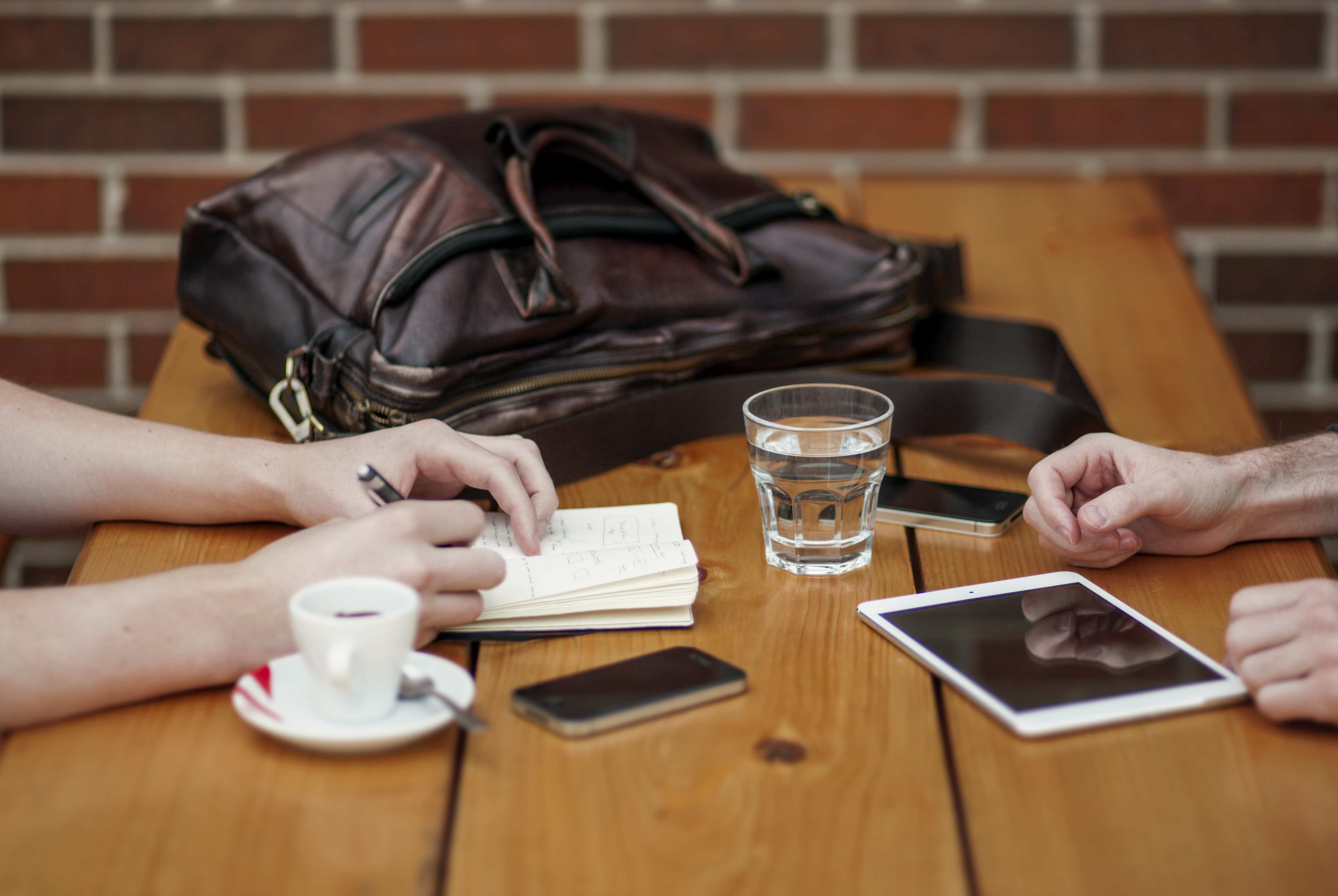 Two people having a meeting while displaying their iphone, ipad, and smartphone on the table.
