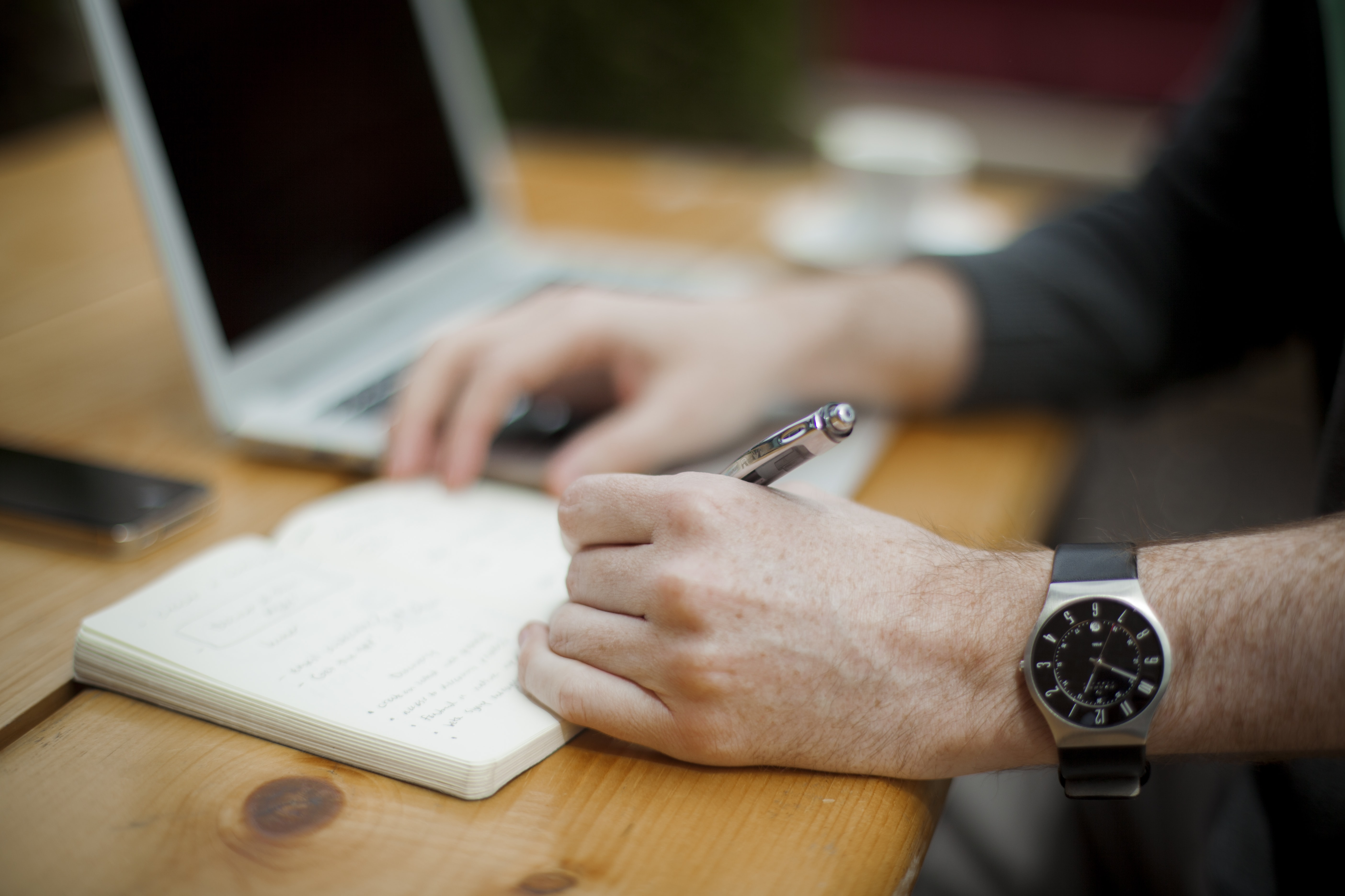 A man's hand with a wristwatch writing a journal on a notebook for publication.