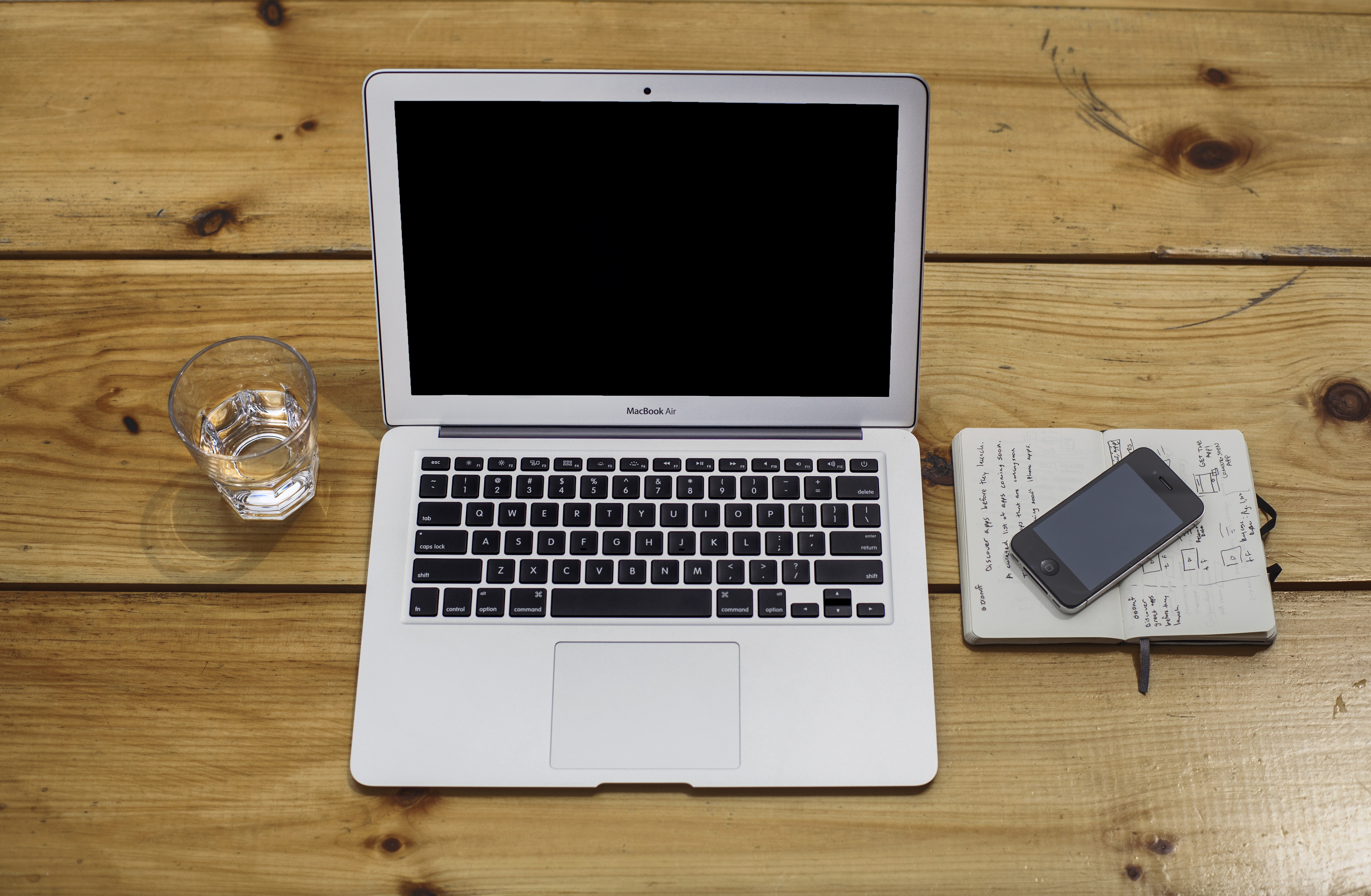 An iPhone, a MacBook and a glass of water on a wooden surface