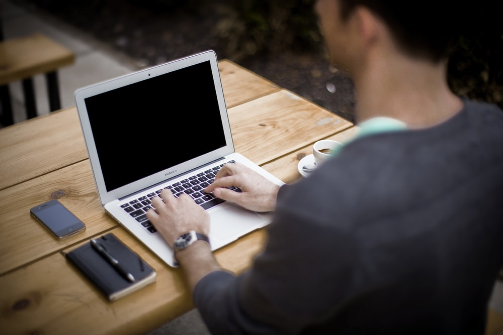 man in front of laptop computer in shallow focus photography