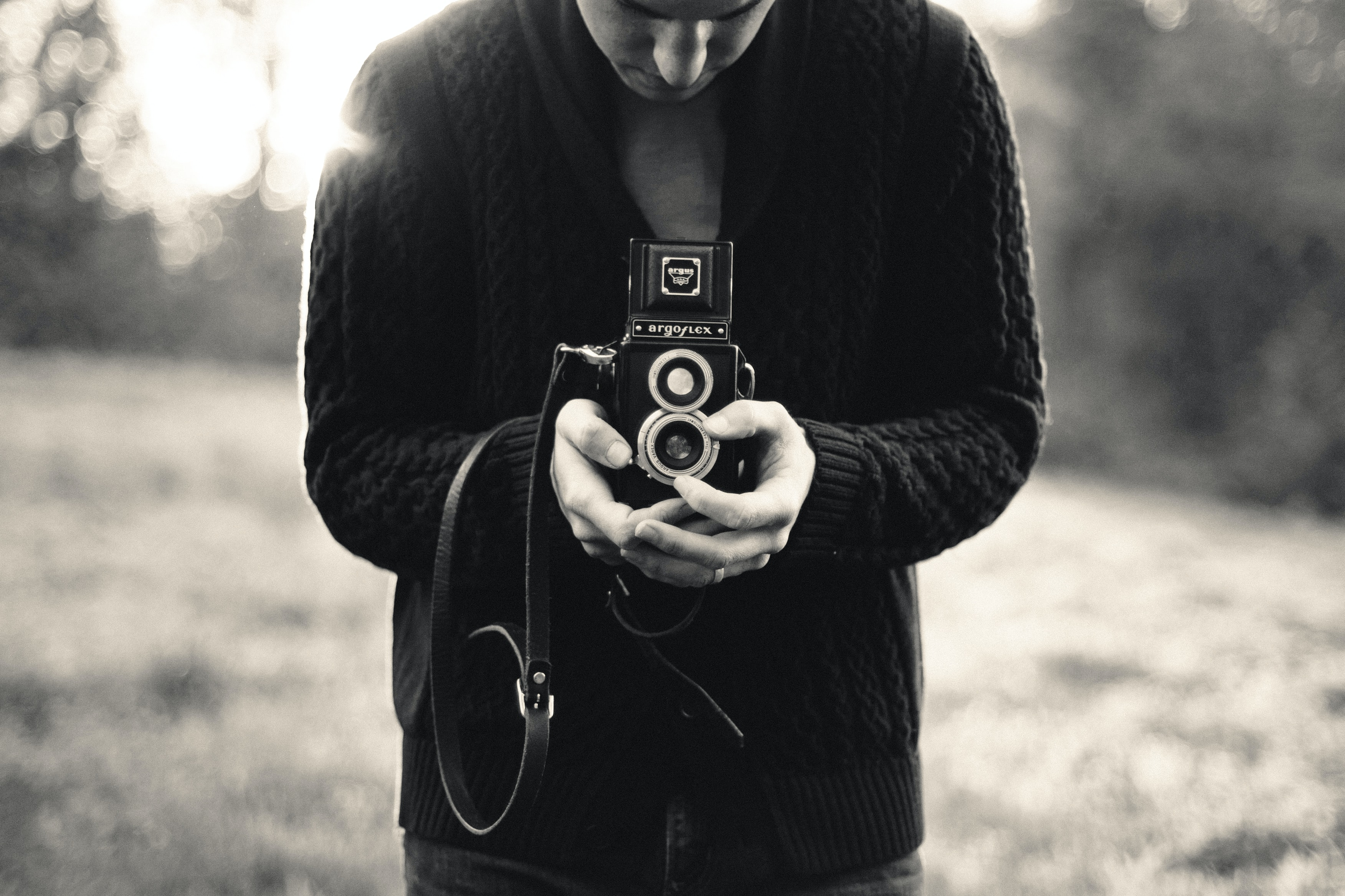 Black and white shot of man in black cardigan holding vintage camera with grass in background