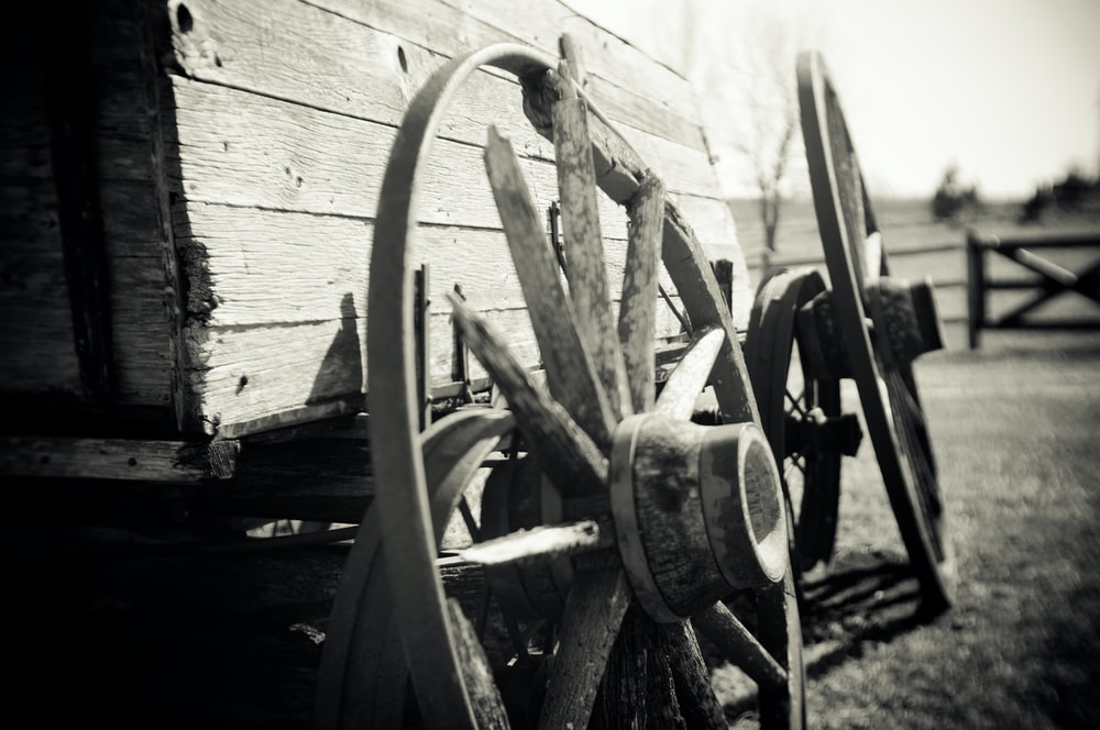 grayscale photo of wagon wheel