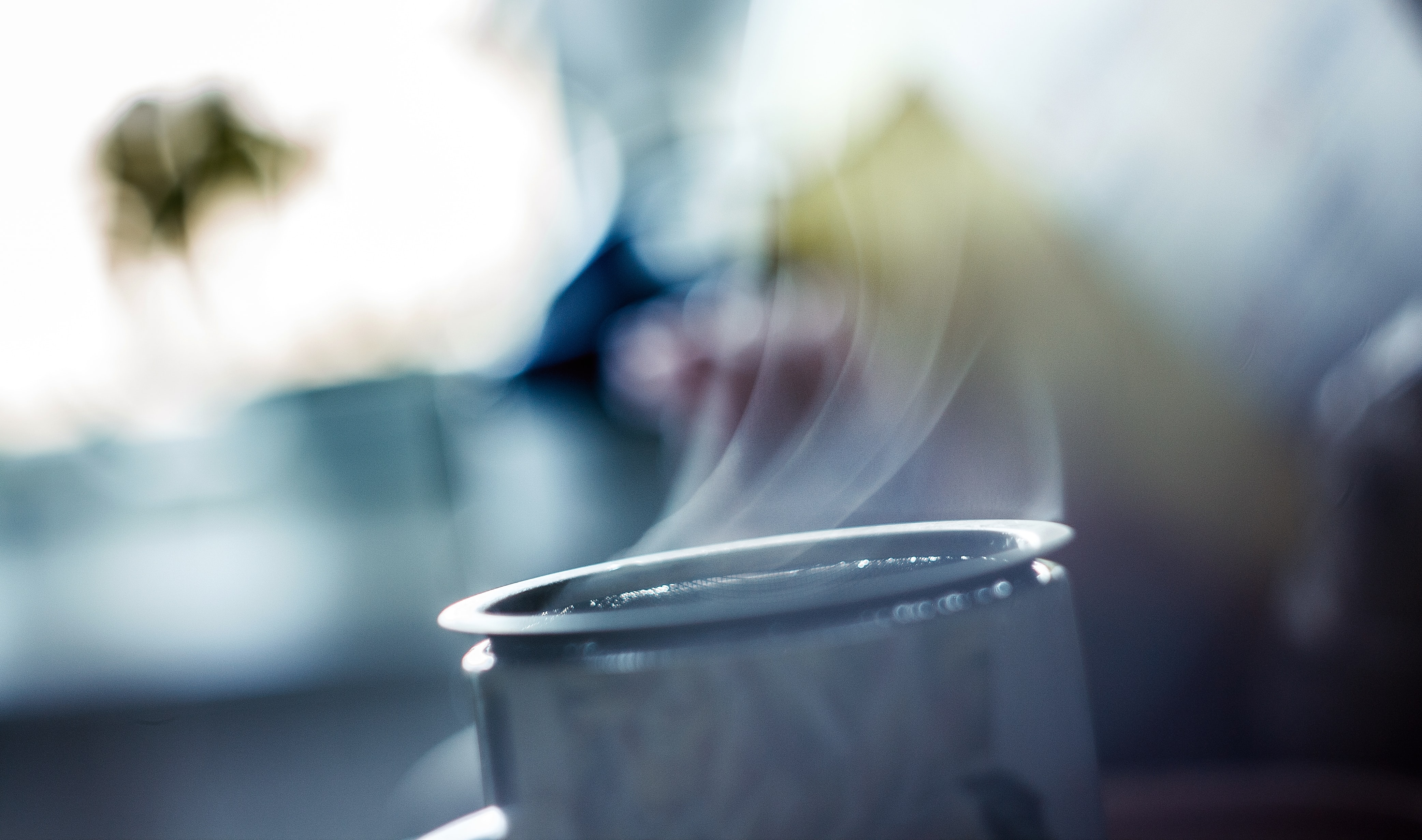 Top of a mug steaming with a blurred outdoorsy background
