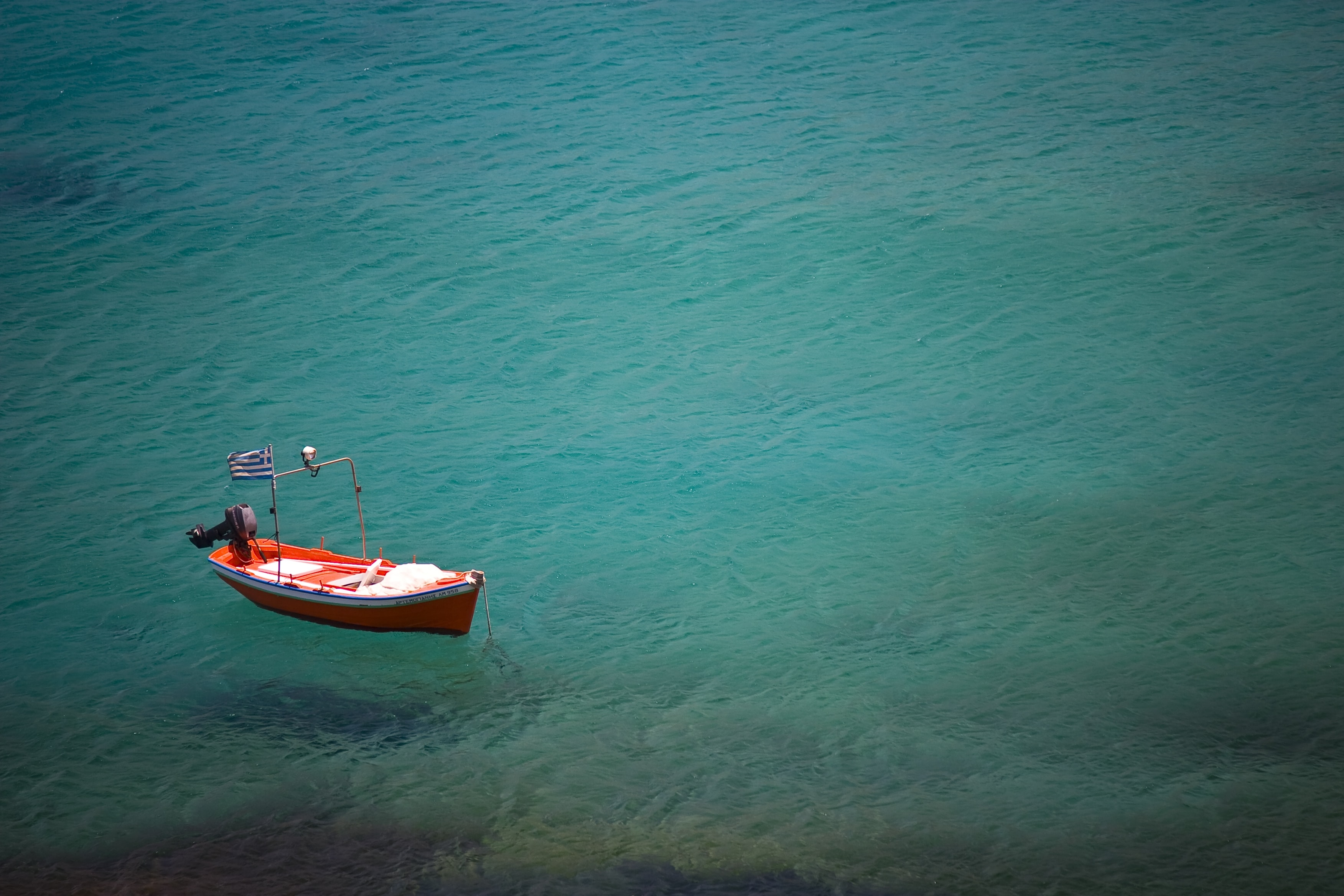 An orange boat with a Greek flag flying, floating on the sea