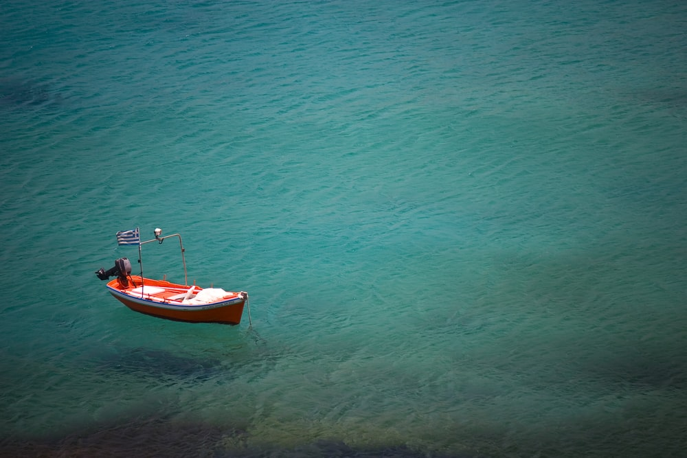 red boat on blue ocean during daytime