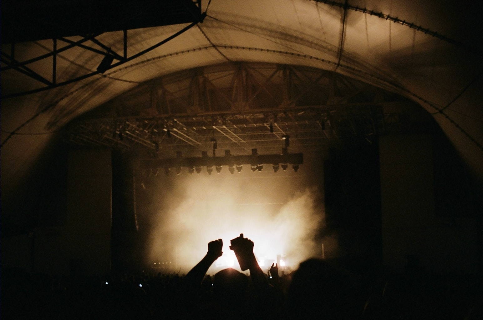Silhouettes of the audience's hands in the air during a concert
