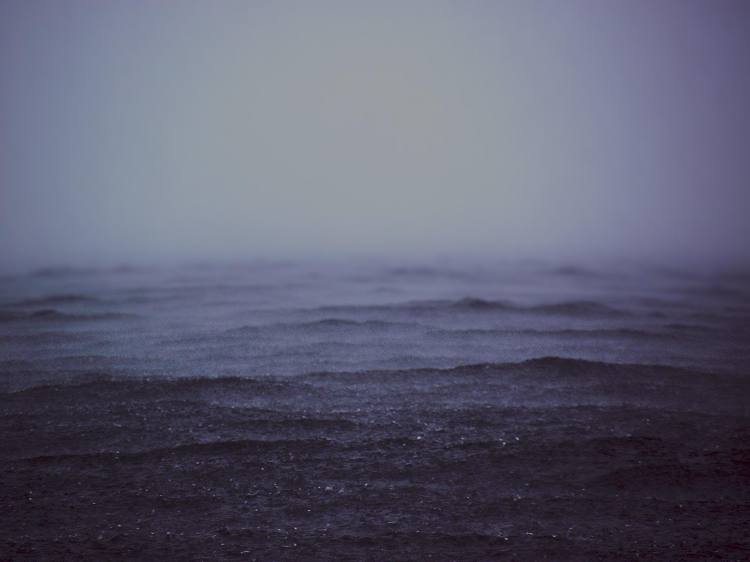 Rain falls into dark stormy waters