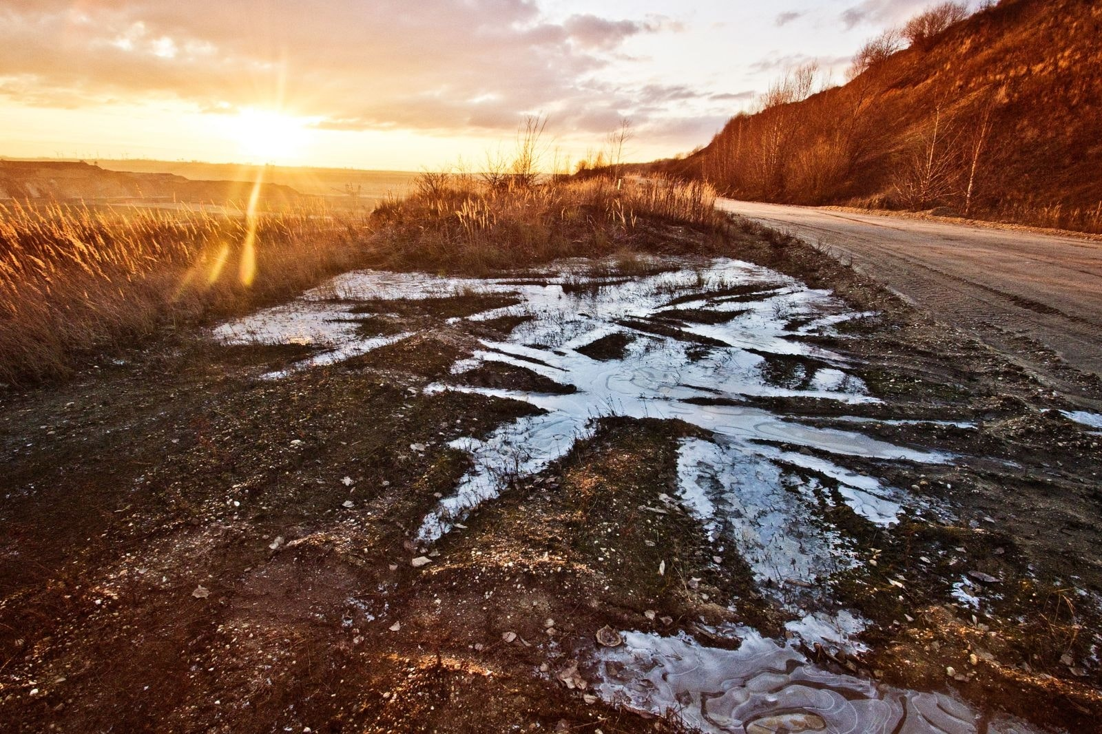 Muddy field along the side of the road during as the sun sets in the horizon