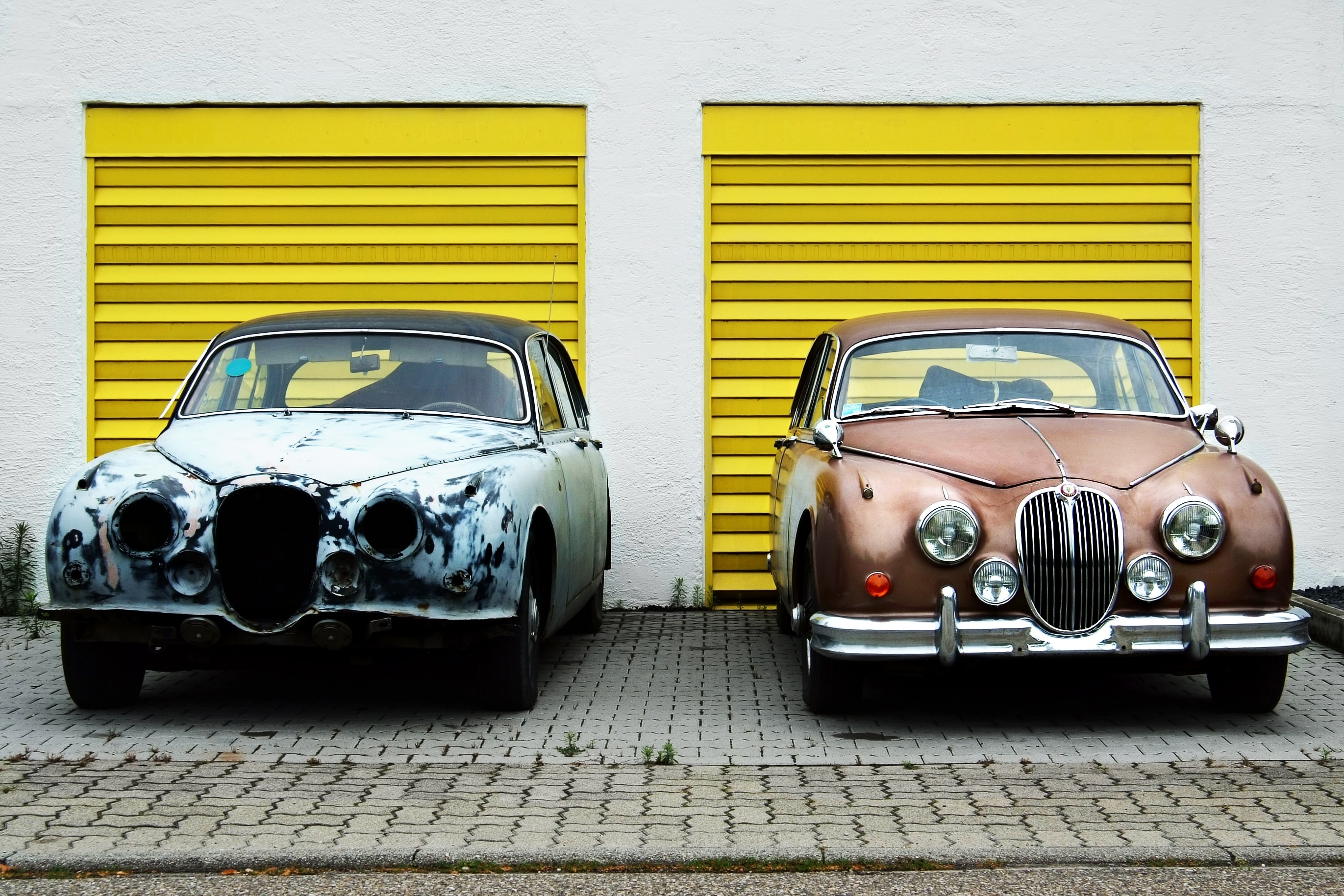 Damaged and repaired antique retro classic cars parked in front of yellow garages