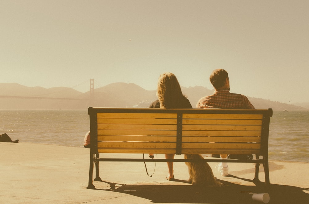 A couple sitting on a bench in San Francisco while their dog sits next to them
