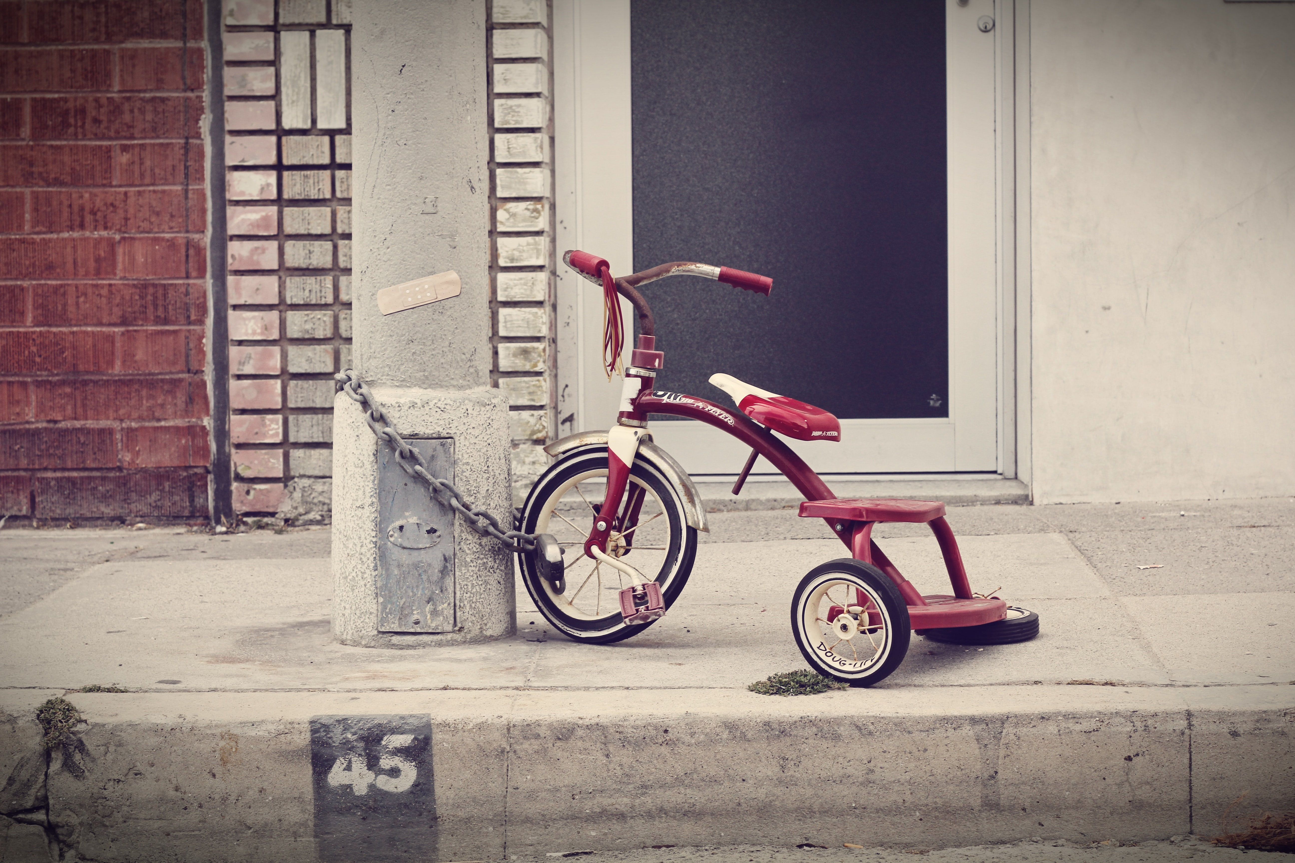 red and white Radio Flyer trike chained on stone post