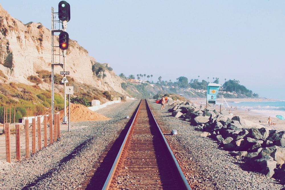 person beside railway near beach