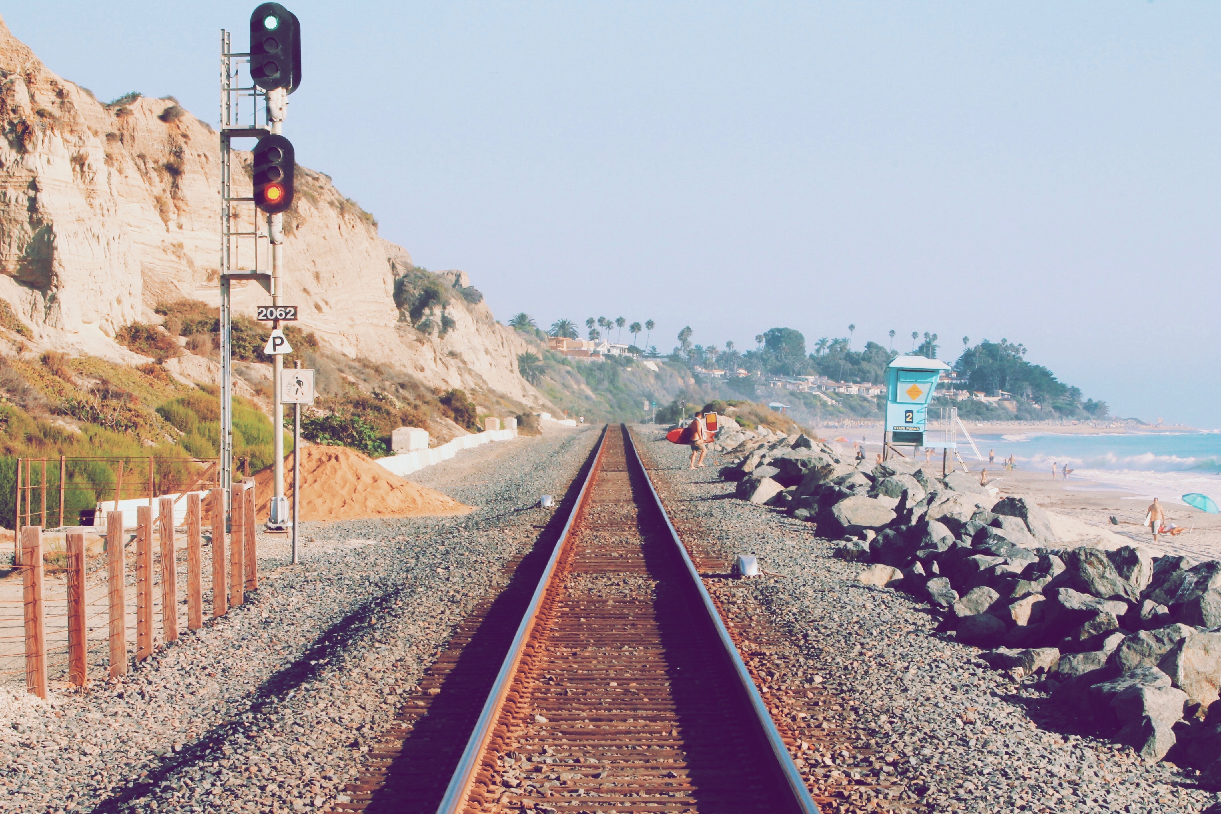 person beside railway near beach
