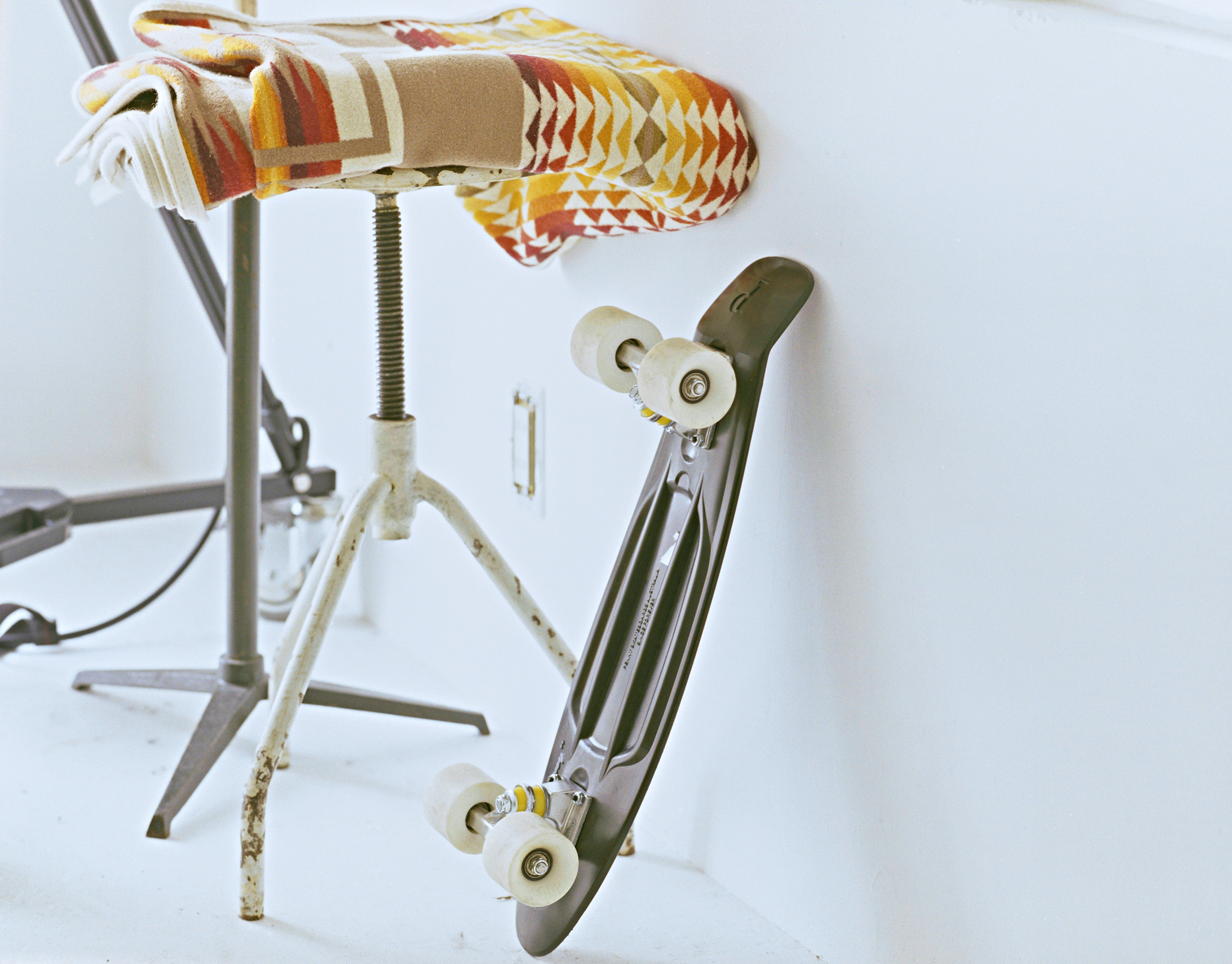 A skateboard is leaning against the white wall next to a footstool with a colorful blanket.