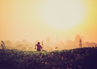 man running towards the city on green grass field during golden time