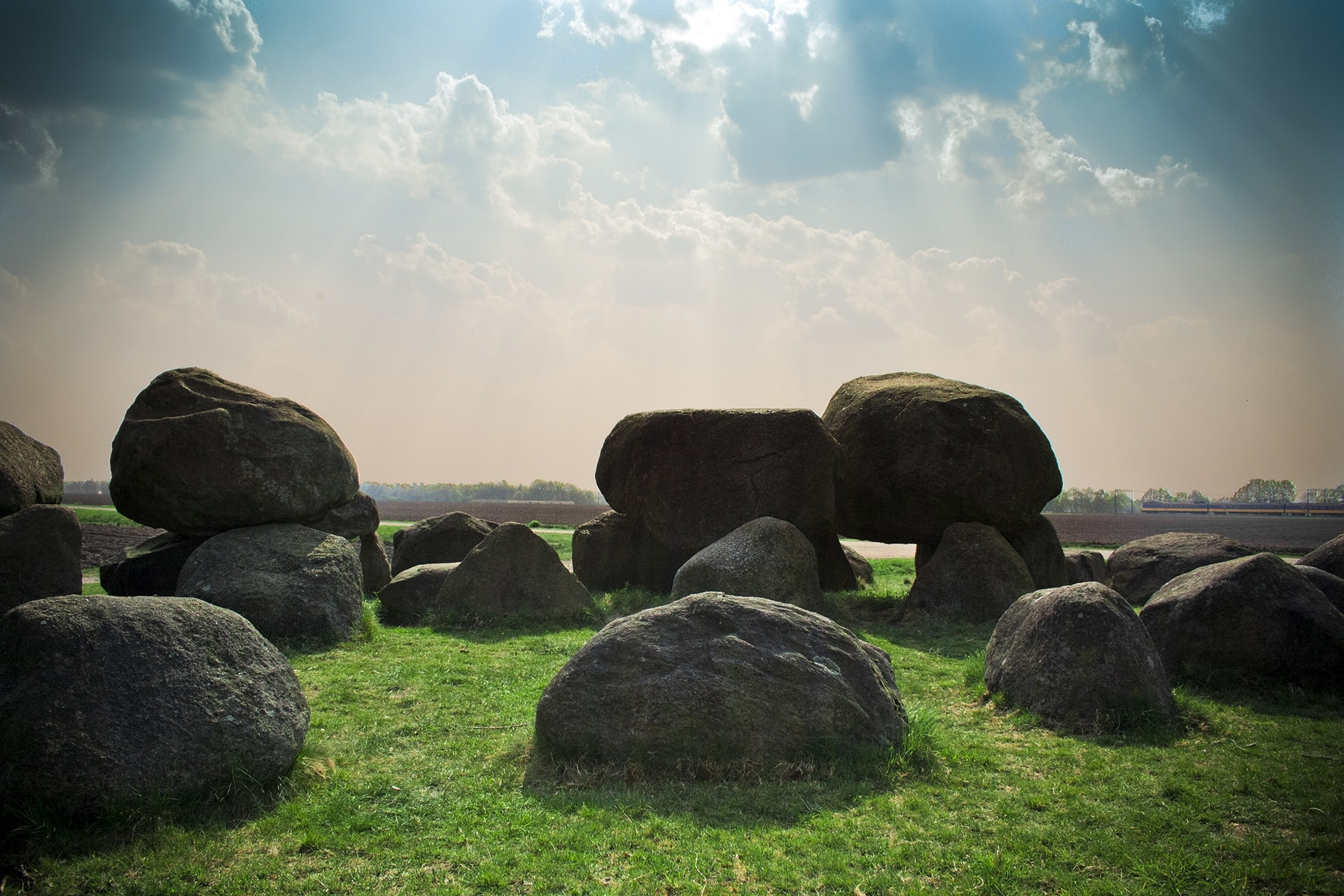 A series of large boulders on green grass under pale sunlight