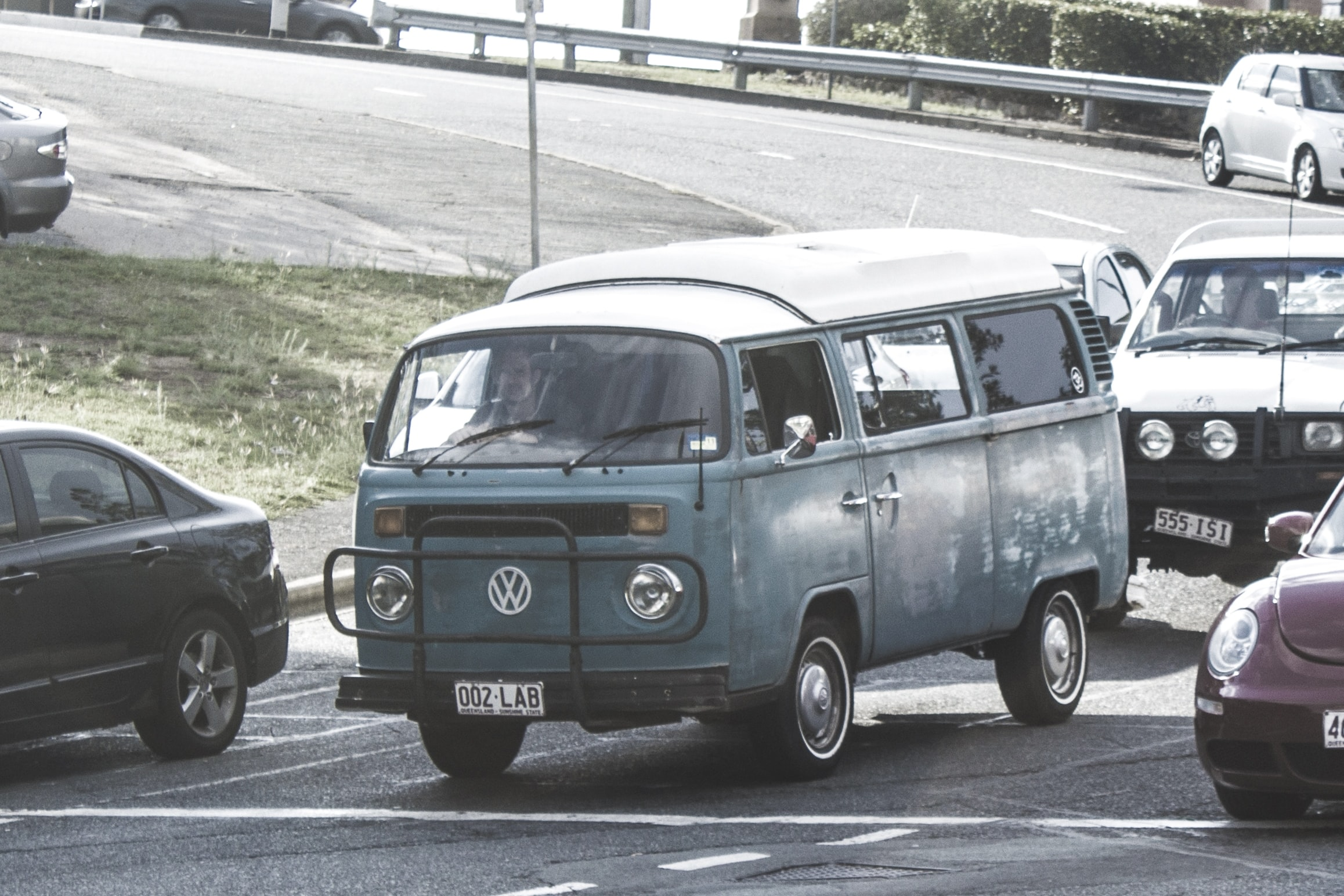 Vintage green Volkswagen camper driving in daytime traffic on road