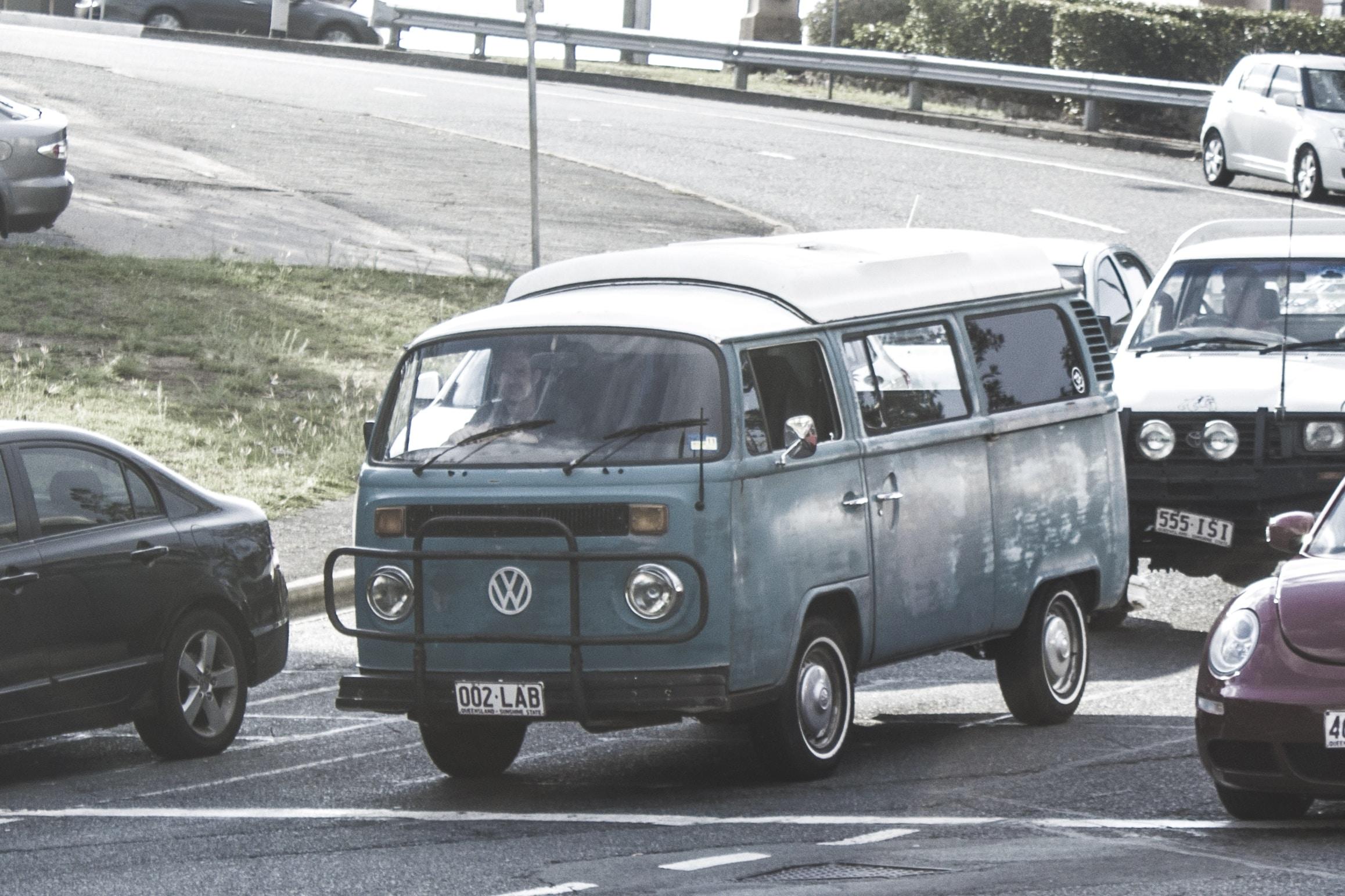 Vintage green Volkswagen camper driving in daytime traffic on road
