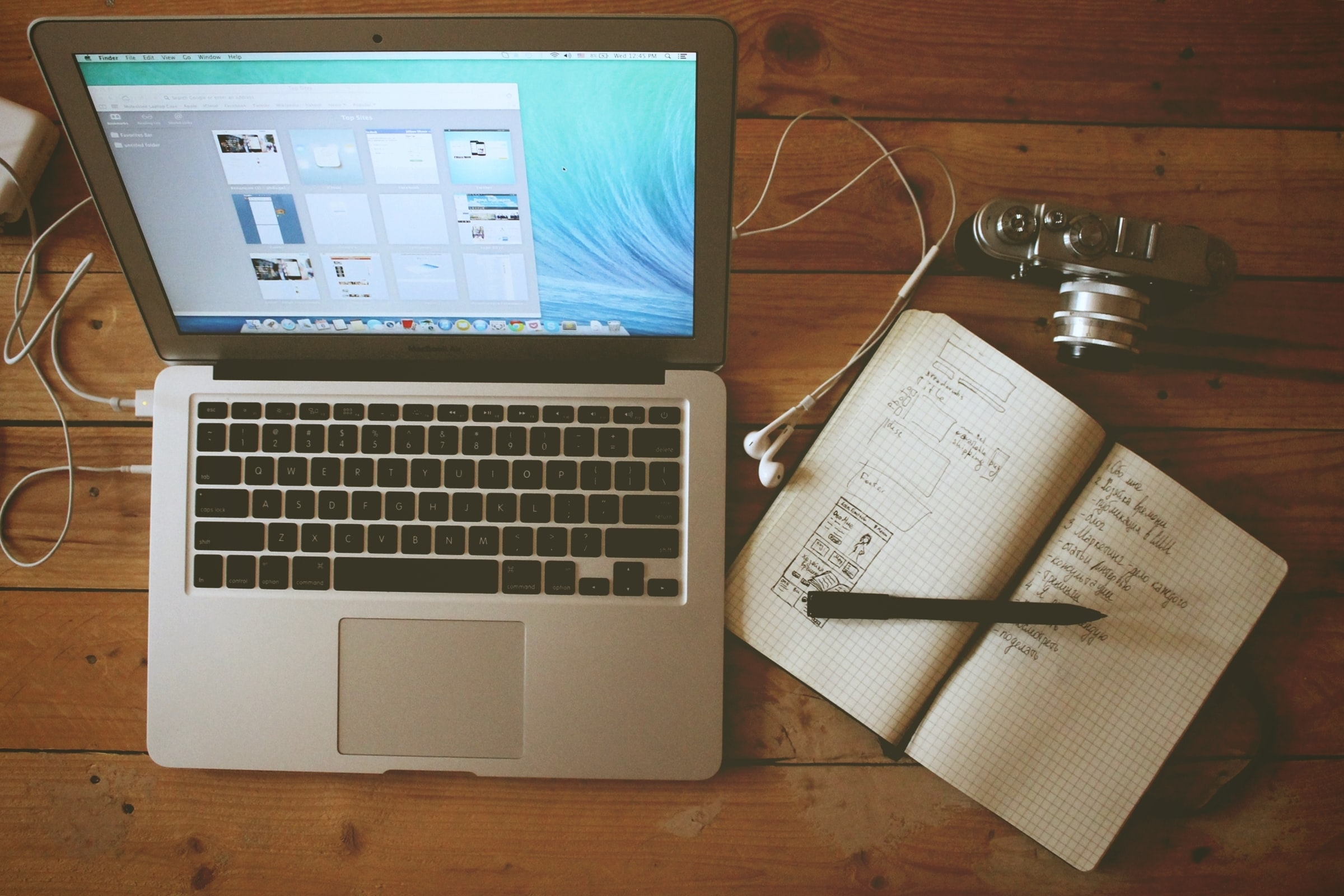 An overhead shot of a notebook and a pen next to a MacBook and a camera