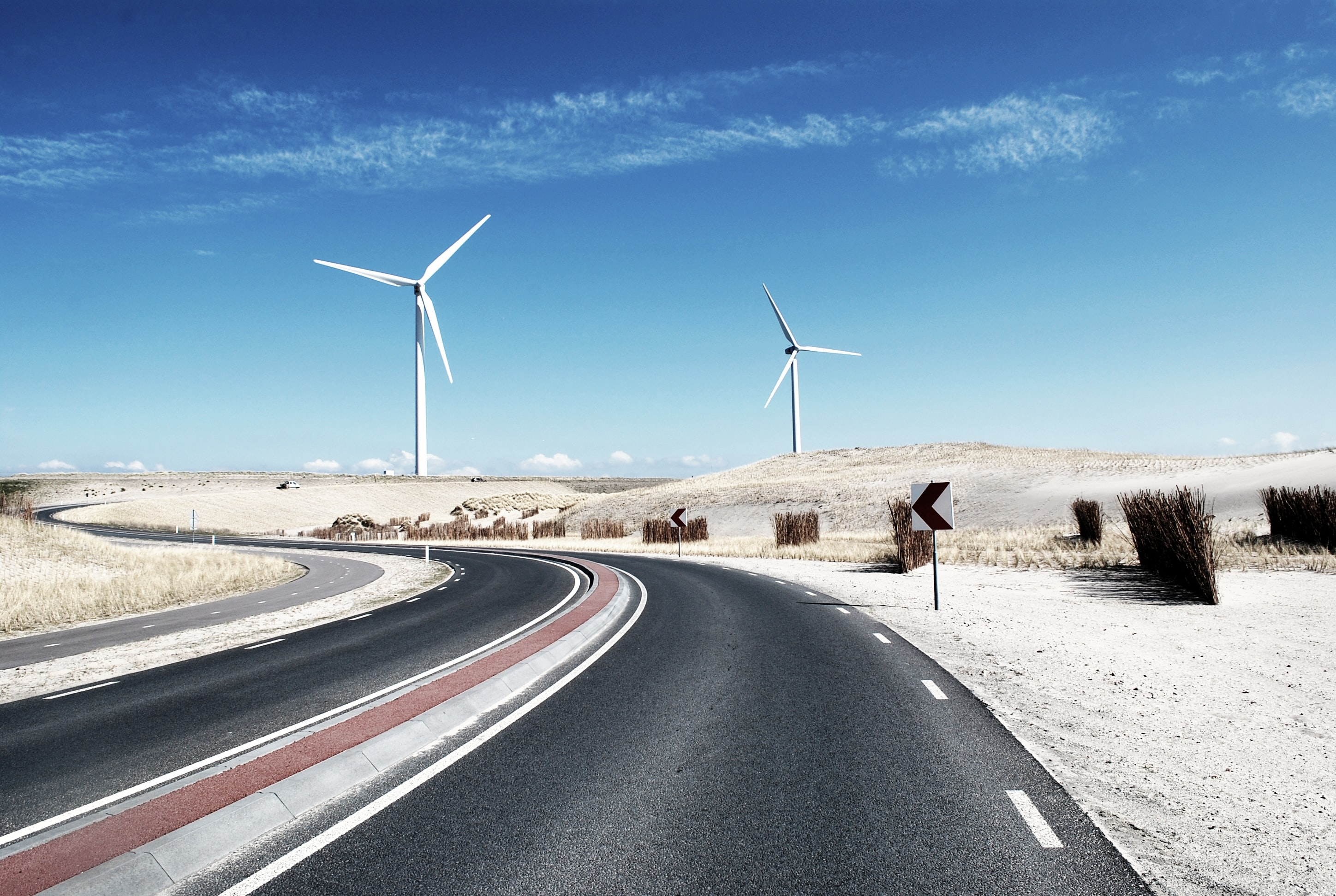 Wind Turbines situated along the paved roads across the desert.