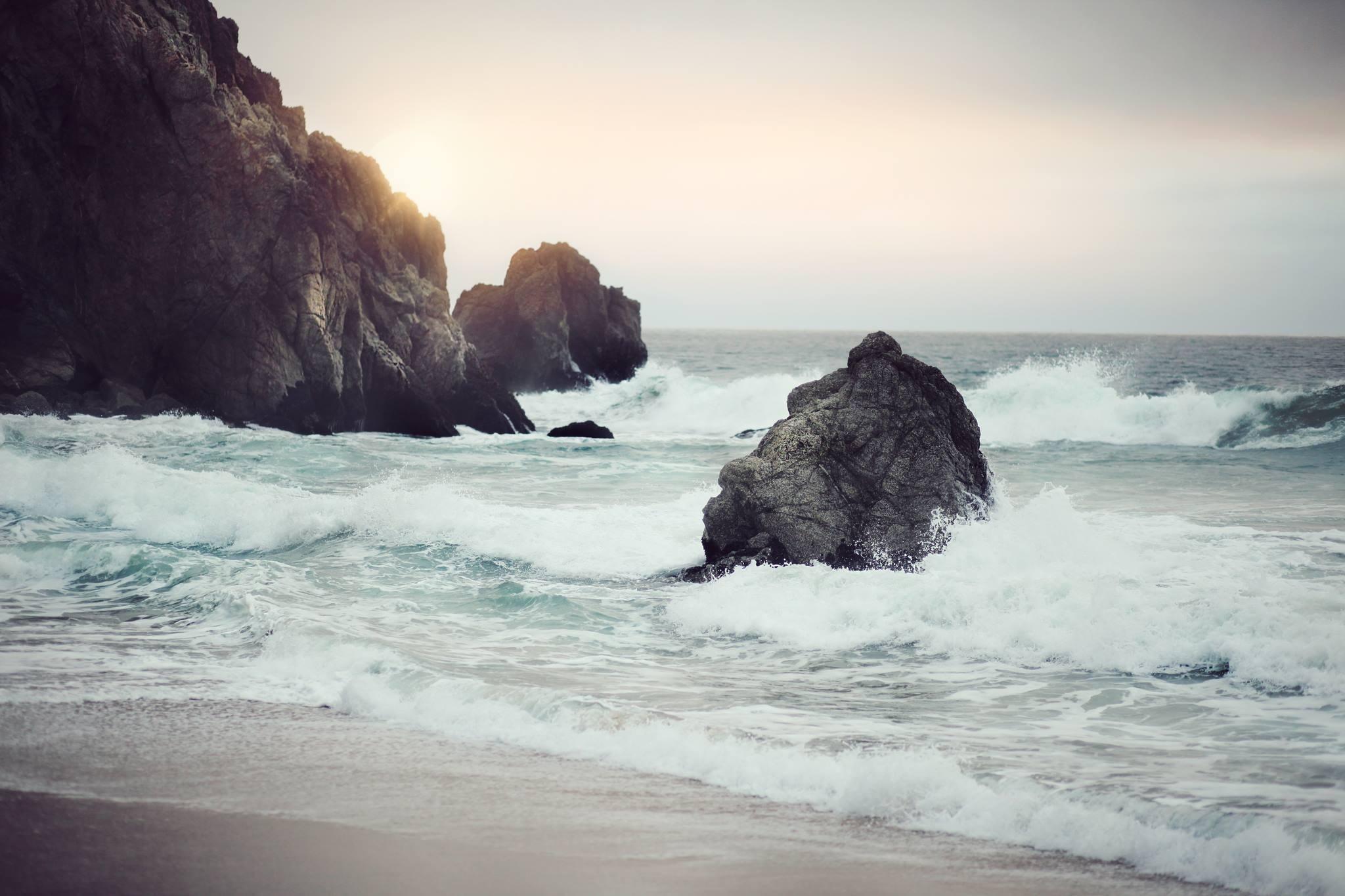 Ocean waves splashing coastal rocks near the sandy beach shoreline