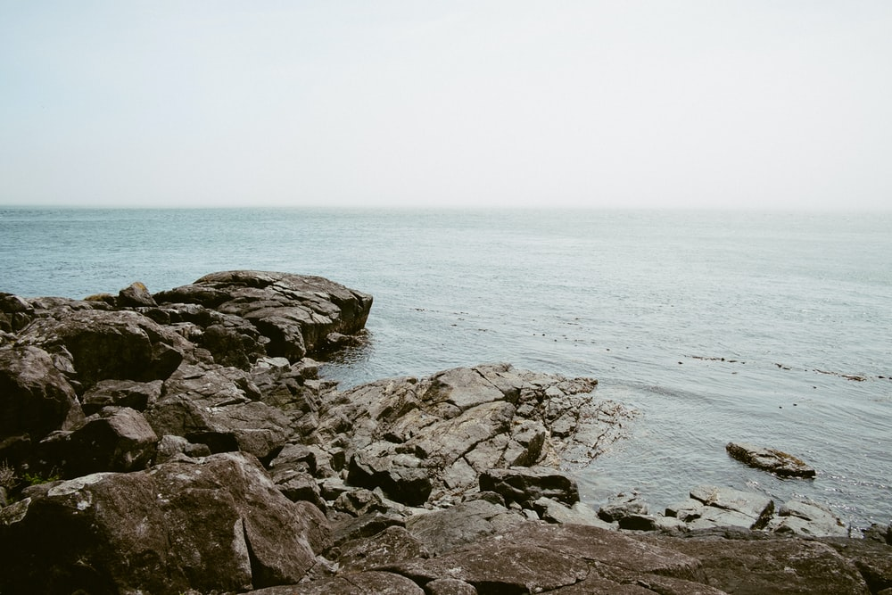 brown rocks beside body of water