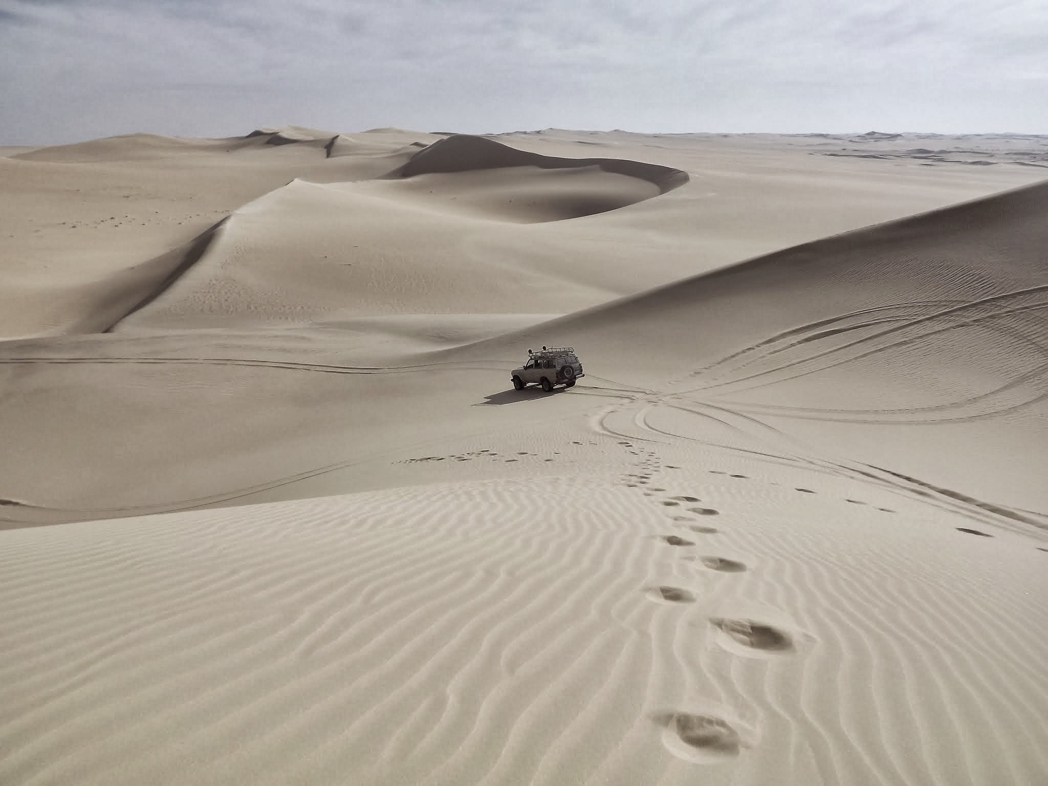 An off-road vehicle driving on the desert with sand dunes stretching to the horizon