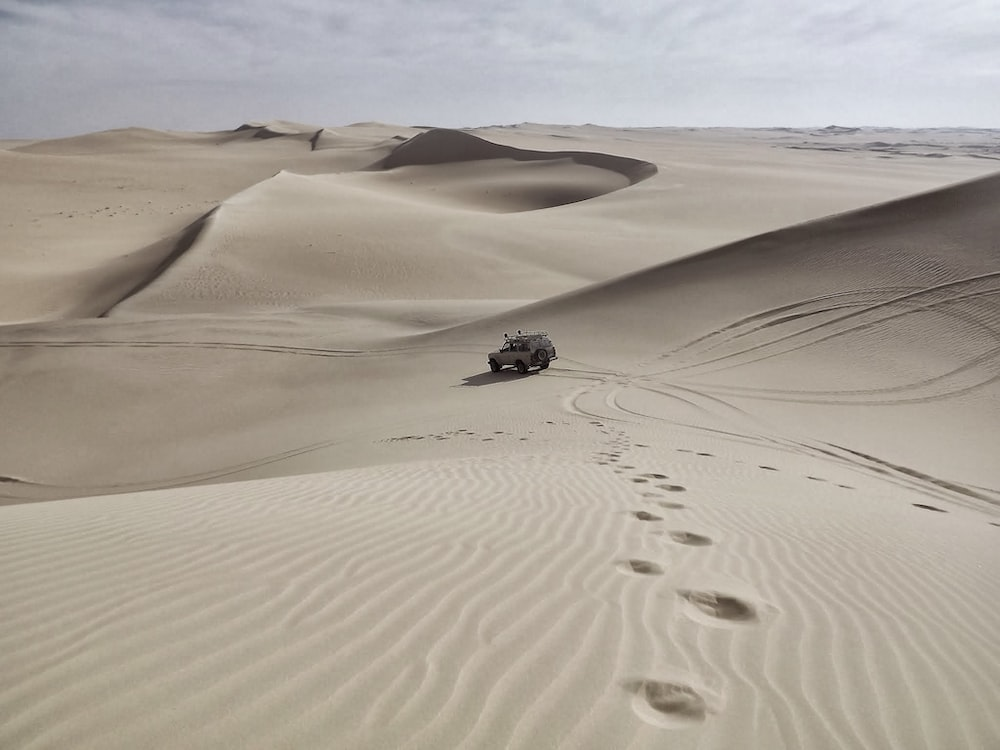 brown vehicle on sand at daytime