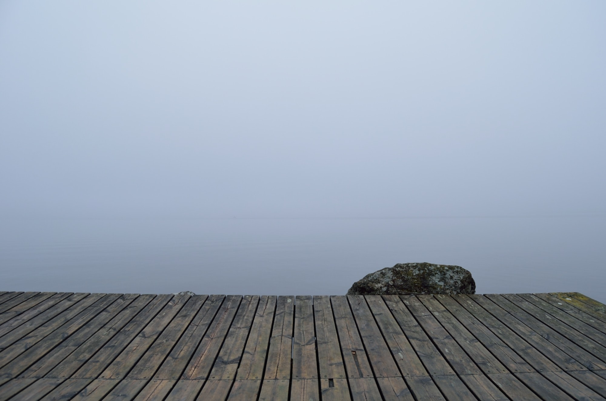 A dock on a foggy, moody day