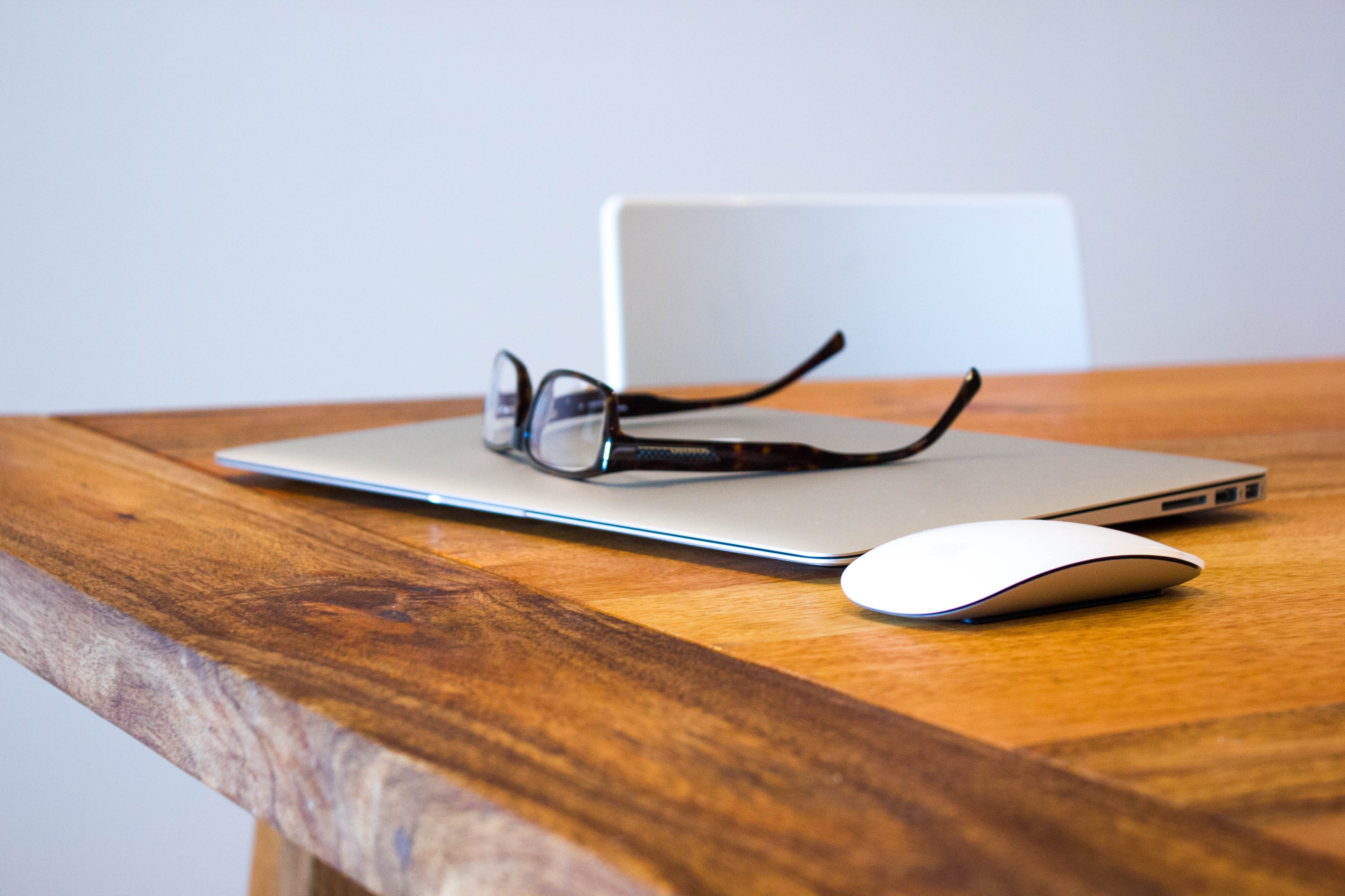 A pair of glasses on top of a laptop next to a mouse on a wooden surface