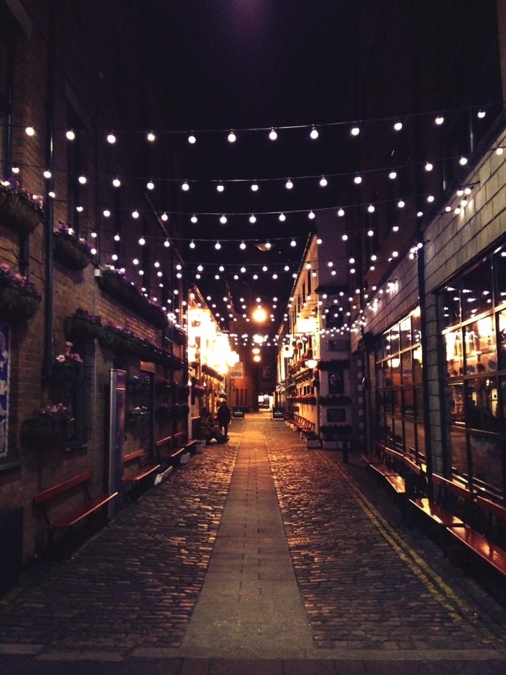photo of narrow street with light bulbs during night time