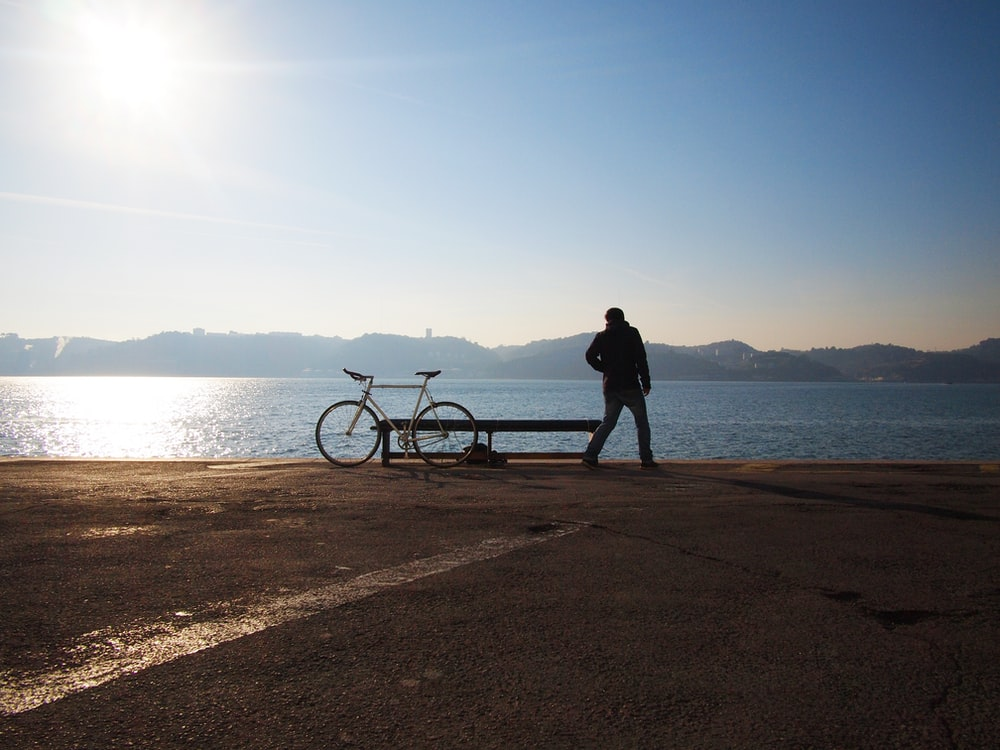 person standing beside of city bicycle