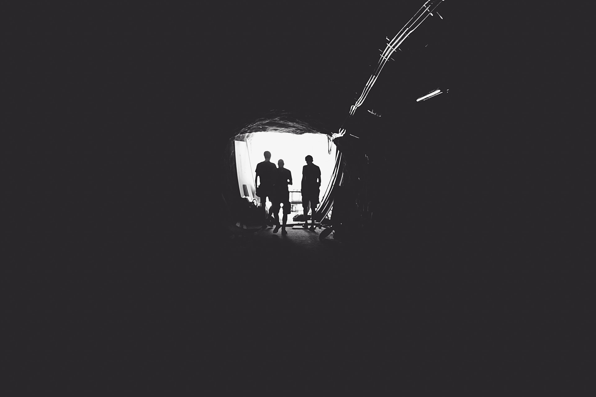 People walking down a dark tunnel into the light