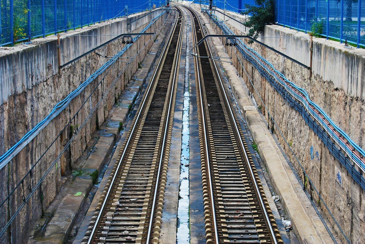 Old train tracks form lines against stone walls in the city