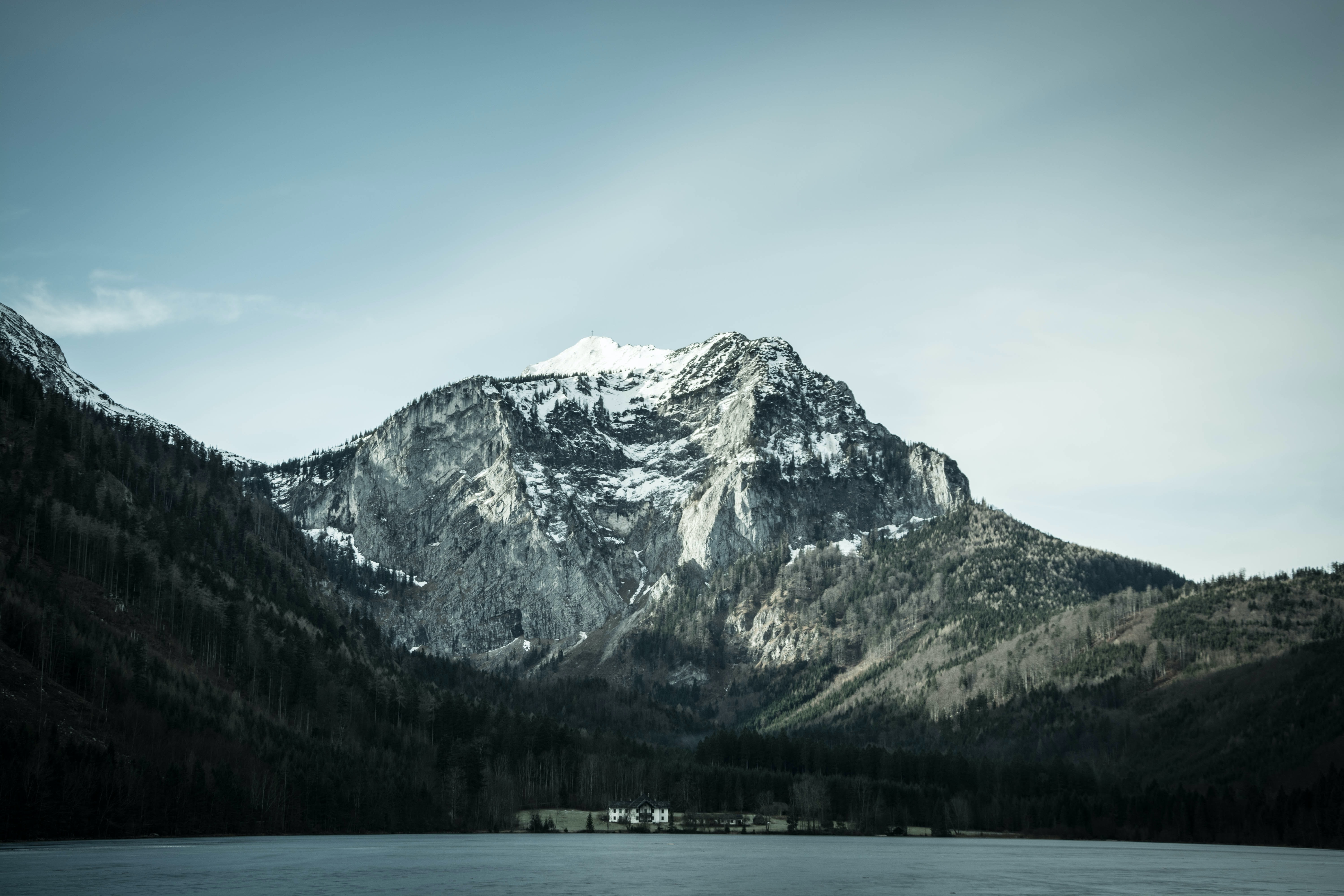snow-covered mountain near body of water