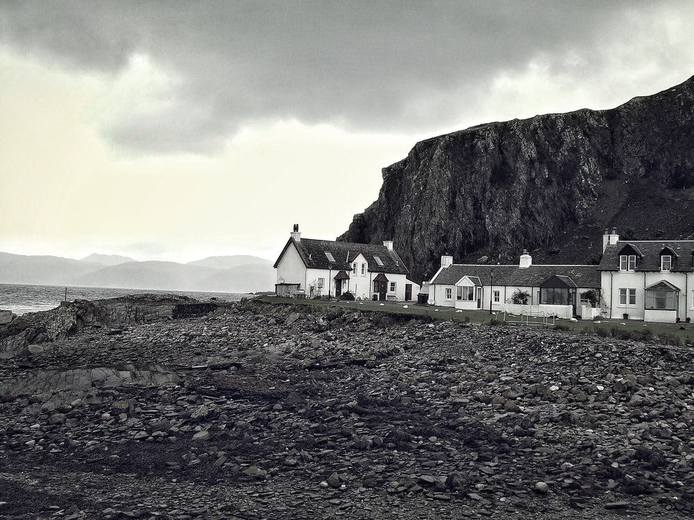 grayscale photography of houses near rocky mountain and body of water