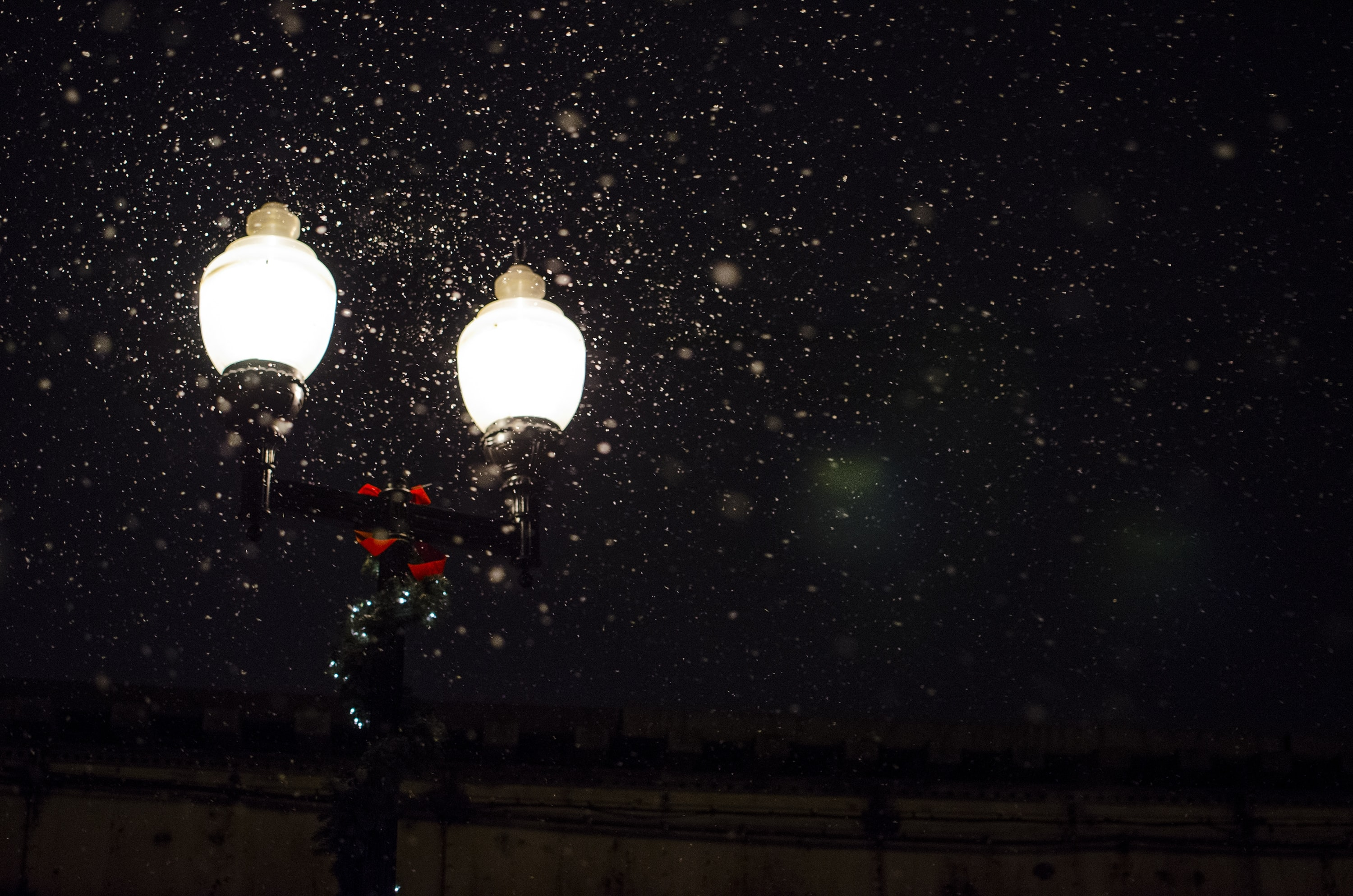 Lit up black lamppost in night sky illuminating specks of snow