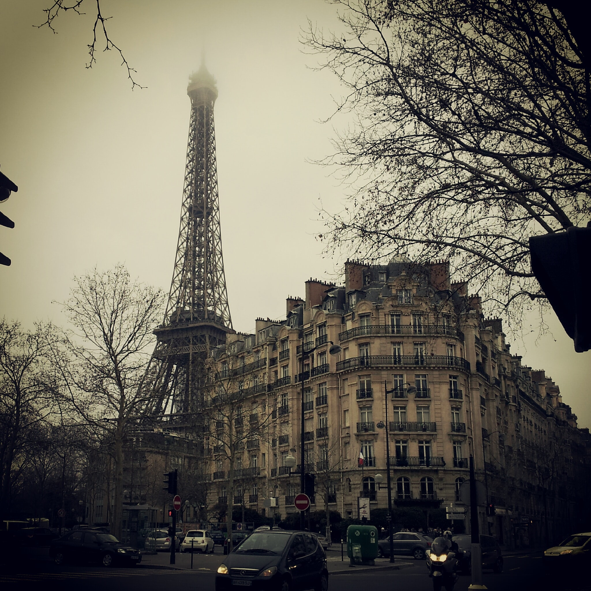 A sepia-toned cloudy view of the Eiffel Tower in Paris from the street