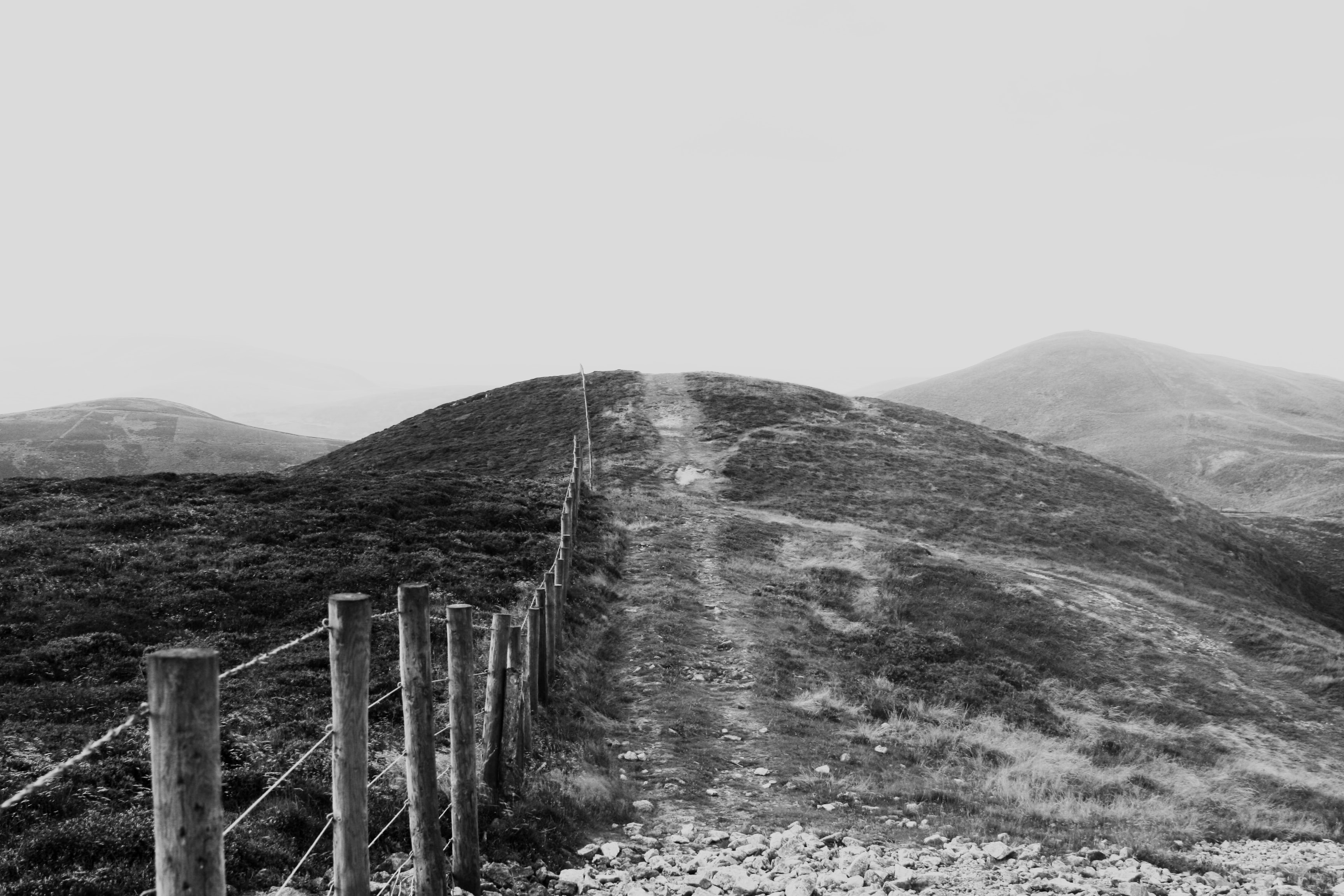 Black and white shot of wire fence with wooden posts on grassy hills with clear sky