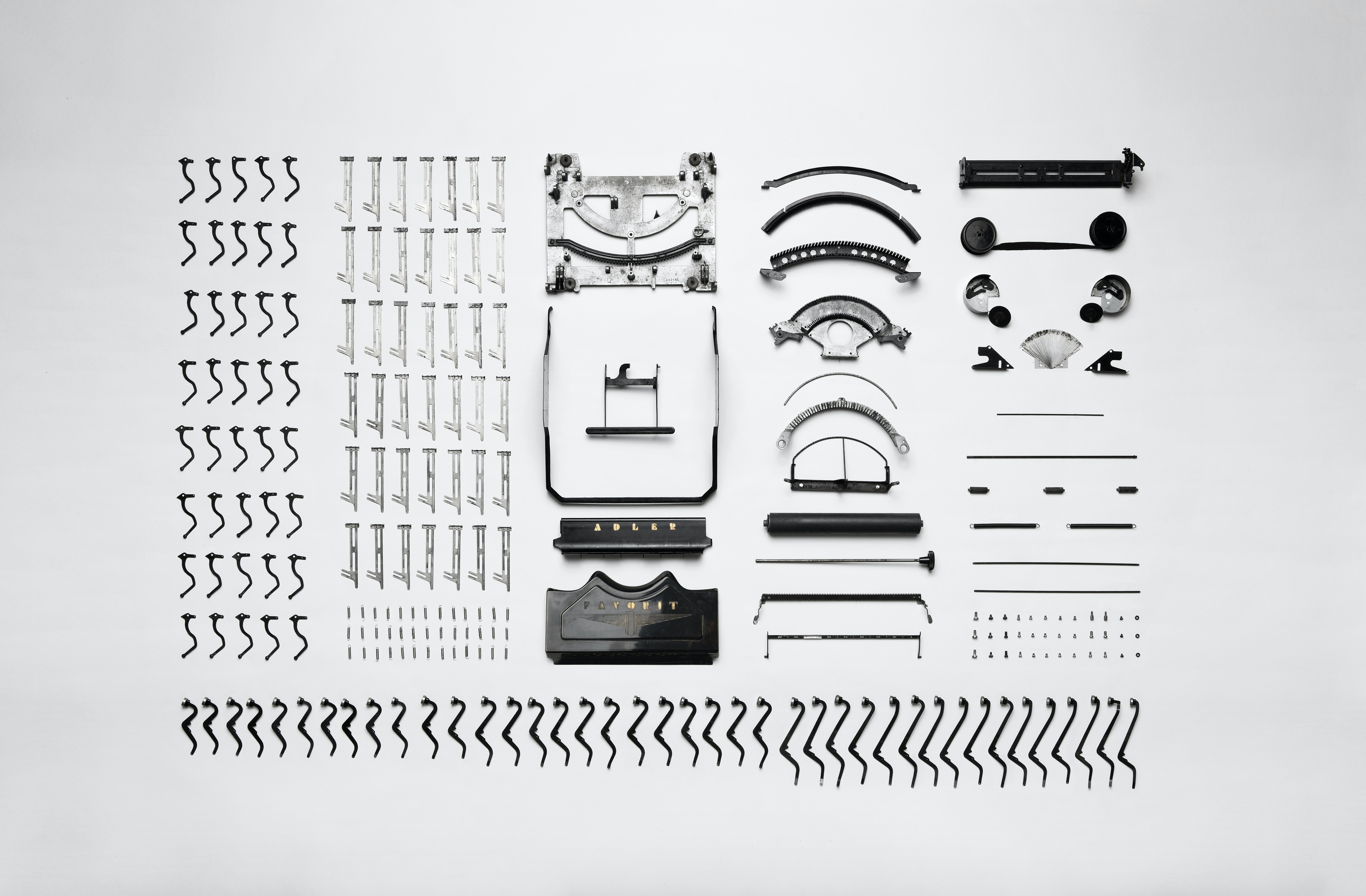 Flat lay photography of the parts of a vintage Adler typewriter.