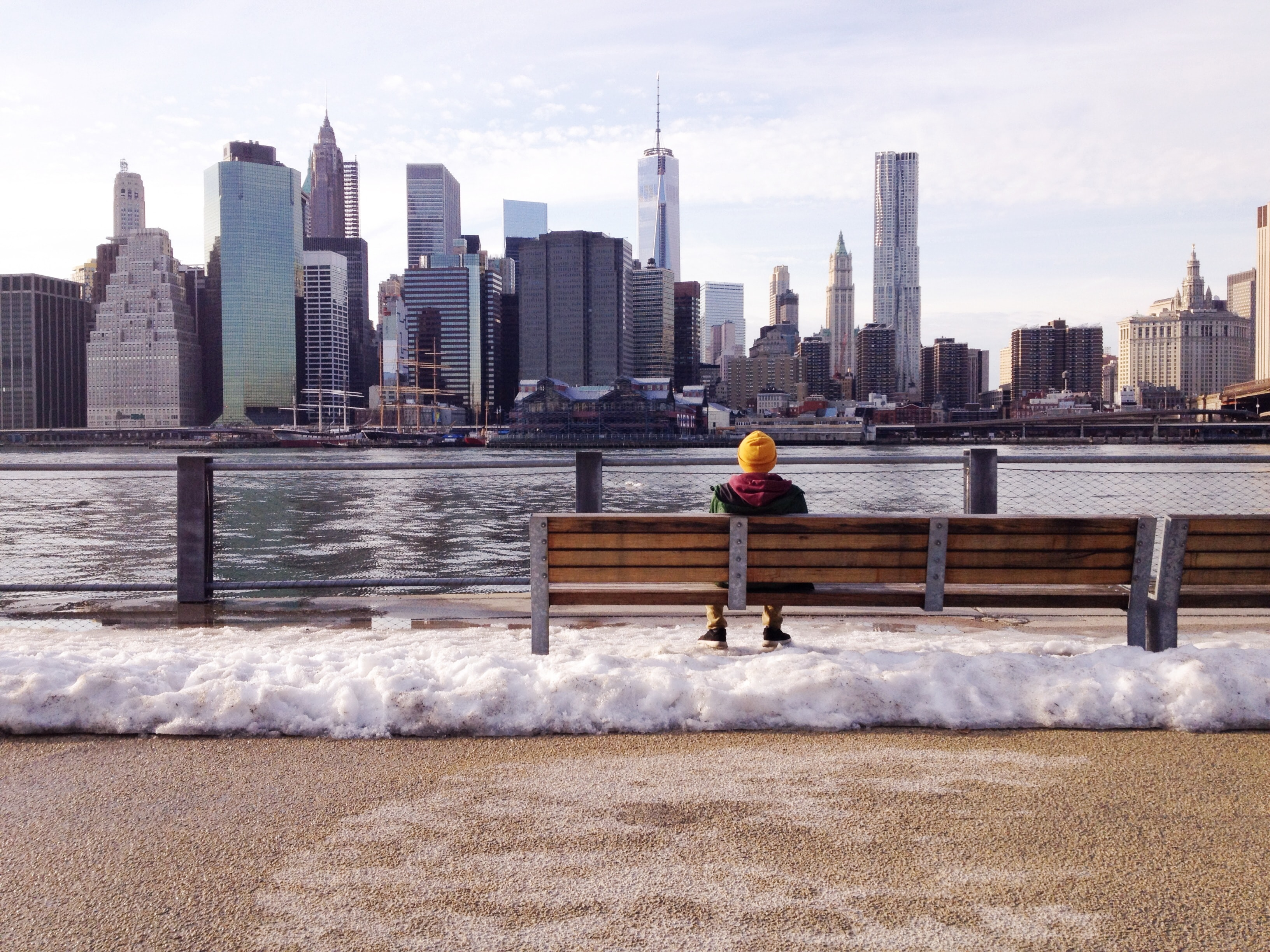 Person sits on a bench looking at the water and skyscrapers of New York City