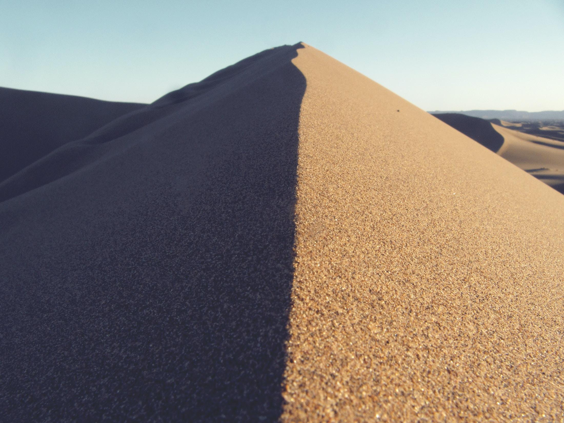 Sand dunes form a symmetrical ridge in the dry desert