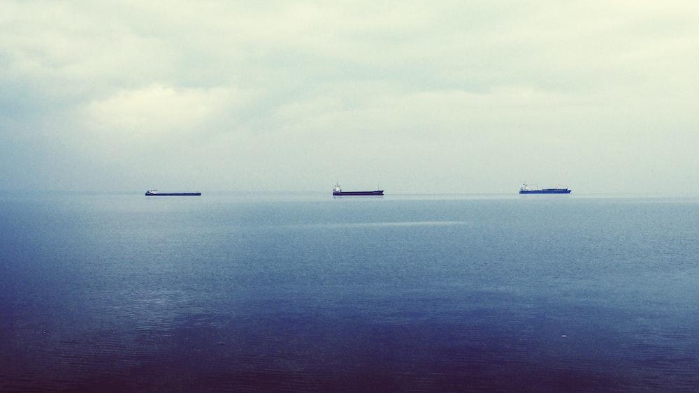 three ship on calm body of water