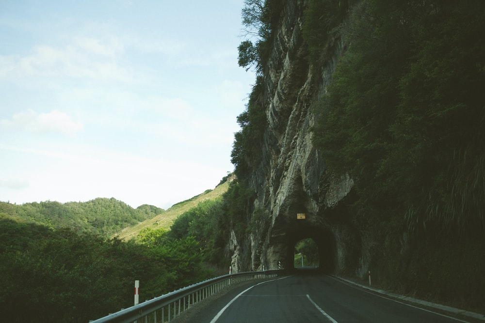 road beside mountain with tunnel