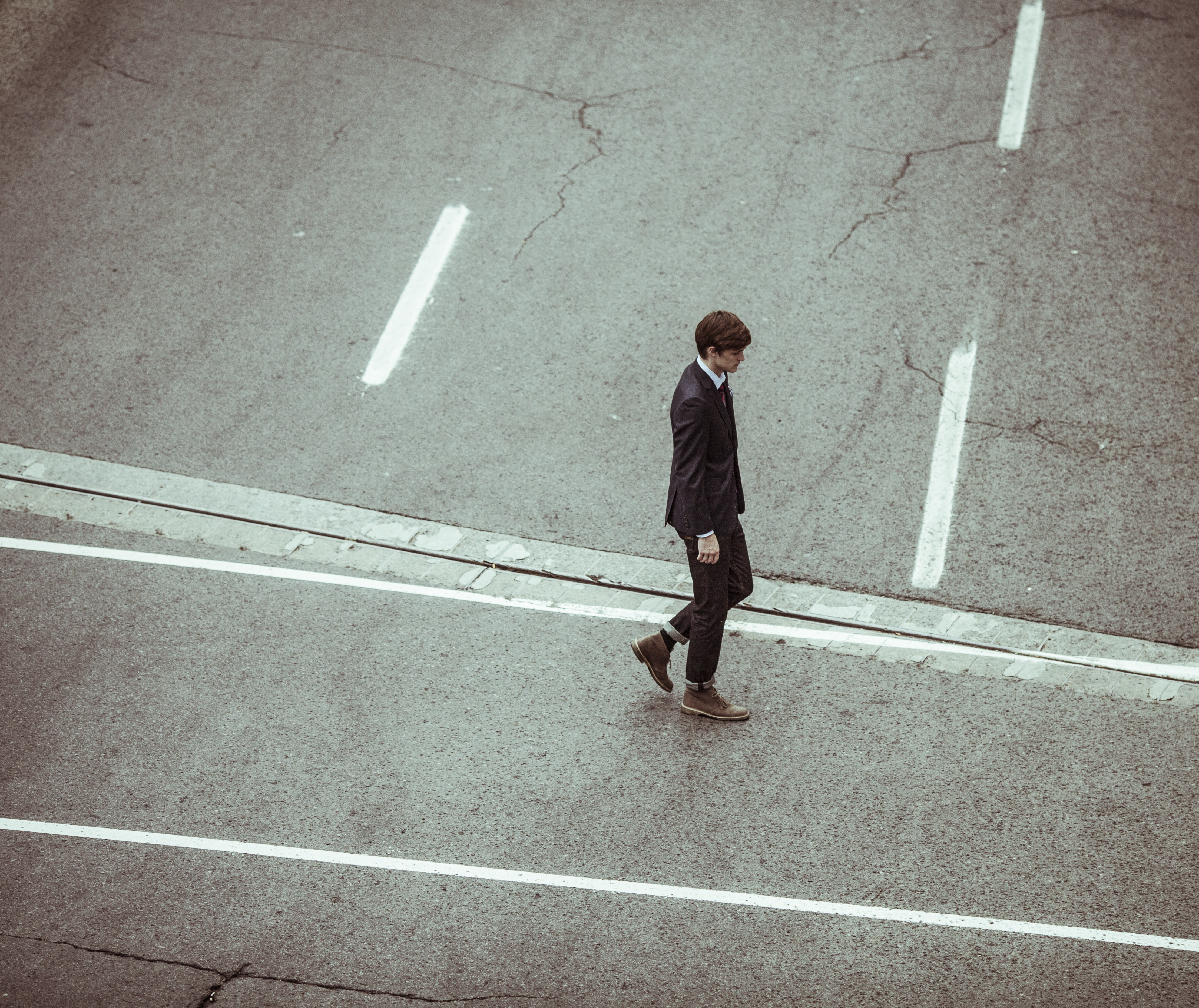An elegant man in a suit crossing the street